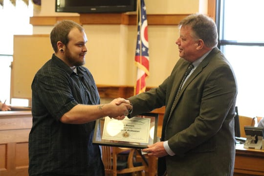 Judge Bruce Winters, right, presents a certificate of graduation to Sean Barnett, who completed the Ottawa County Drug Addiction Treatment Alliance Program, or Drug Court.