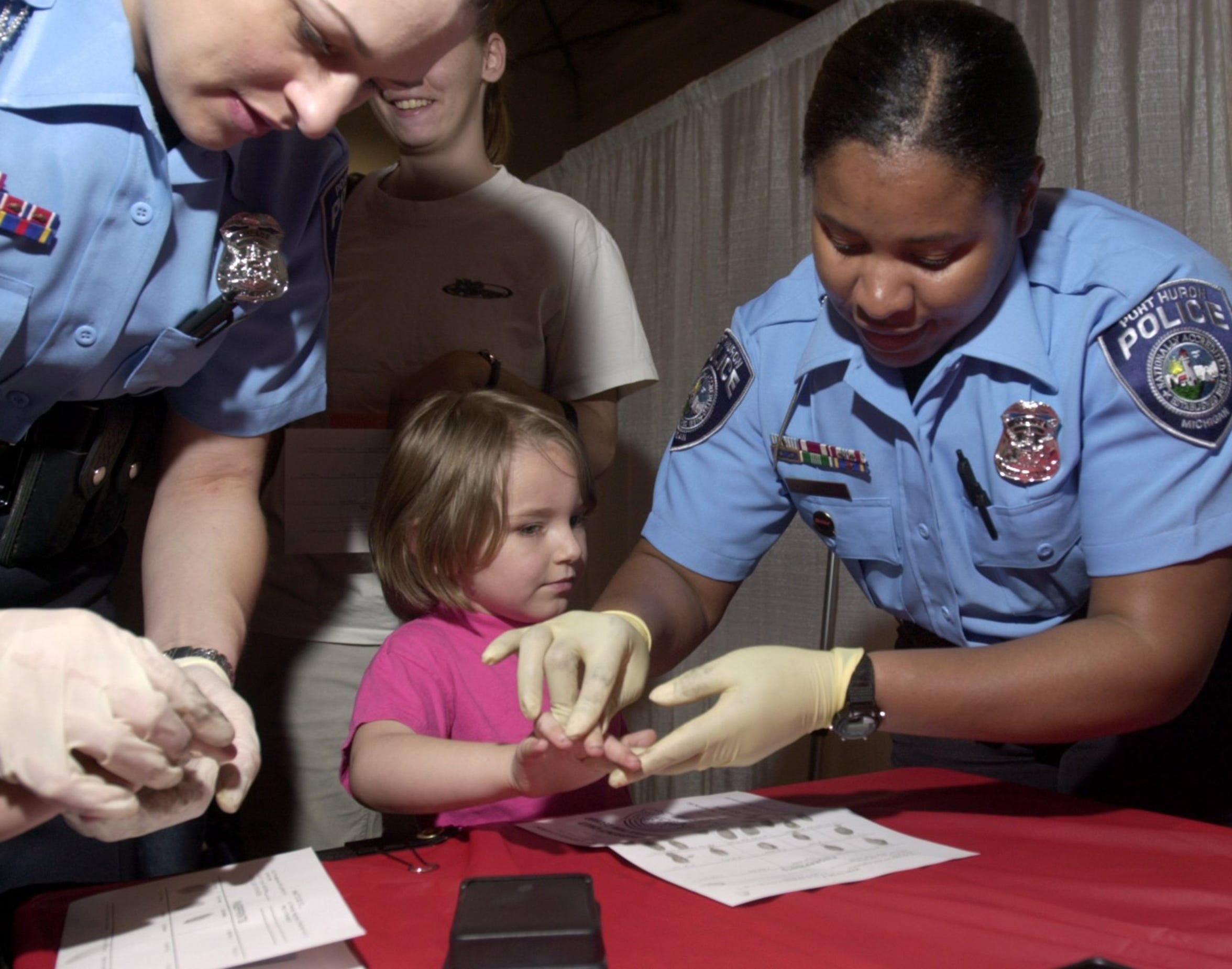 Sgt. Karen Brisby, right, then a Drug Abuse Resistance Education officer, fingerprints a small girl during an event at McMorran Place in 2003, as Capt. Marcy Kuehn, then a community service resource officer, works with another child.