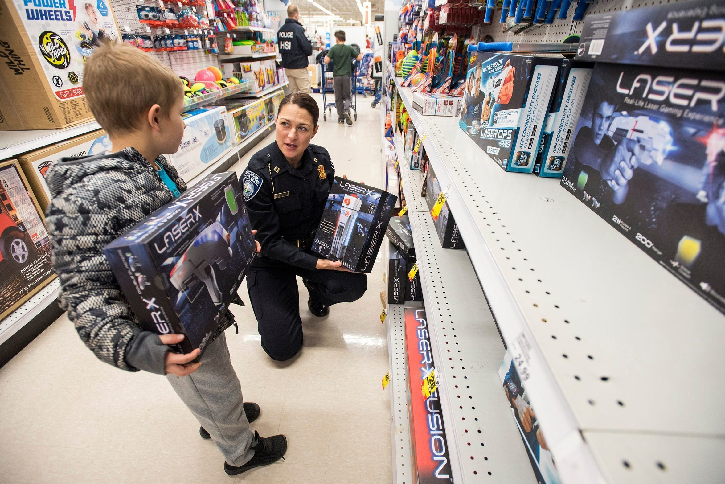 Port Huron Police Capt. Marcy Kuehn, right, helps Adrian Villarreal, 8, shop for a laser gun game at Christmas with a Cop Tuesday, Dec. 11, 2018, at Meijer in Fort Gratiot. Kuehn was promoted to captain from lieutenant in 2018.