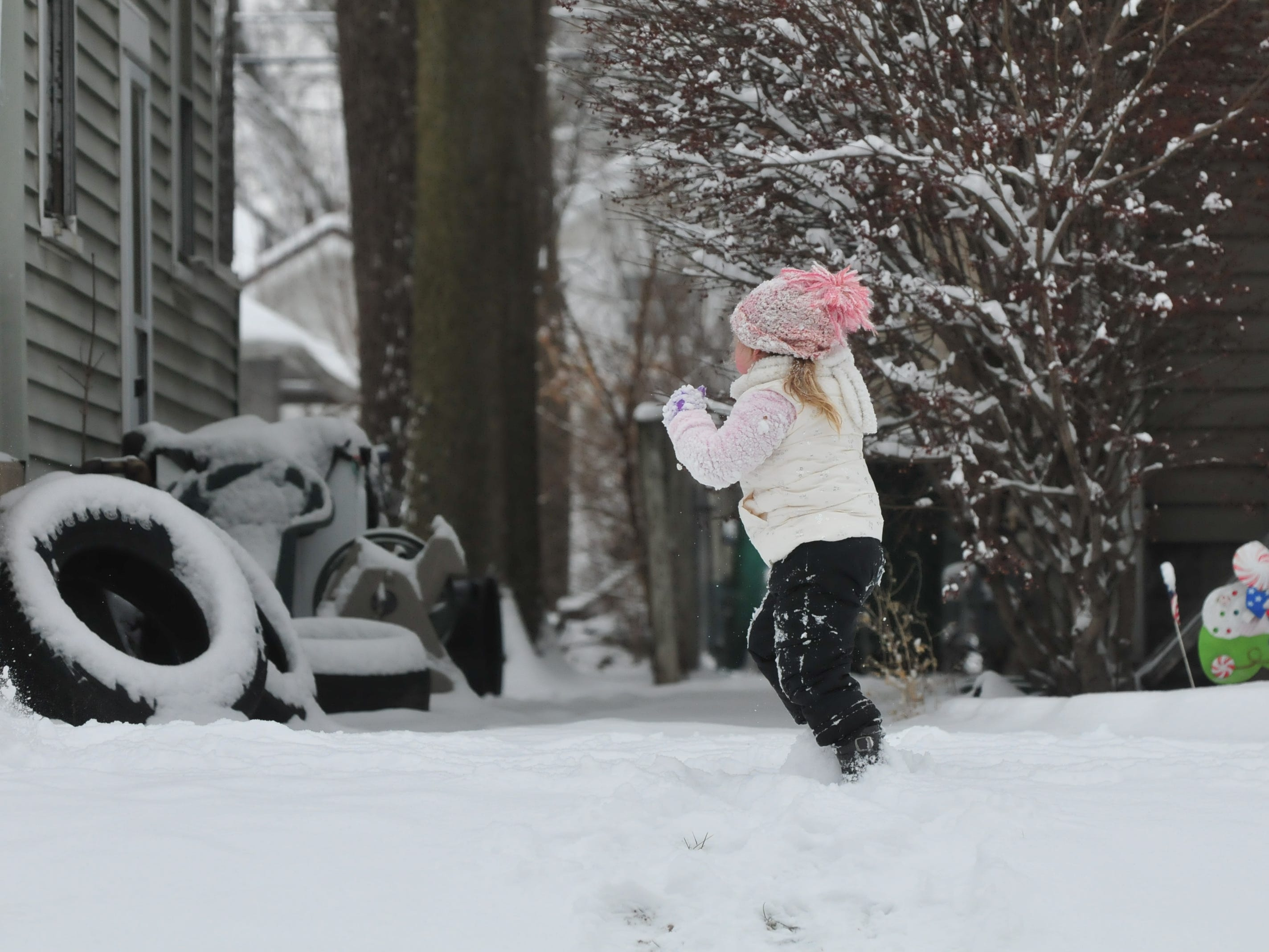 Miah France runs through the snow Friday as she plays with her cousin Kyla France.
