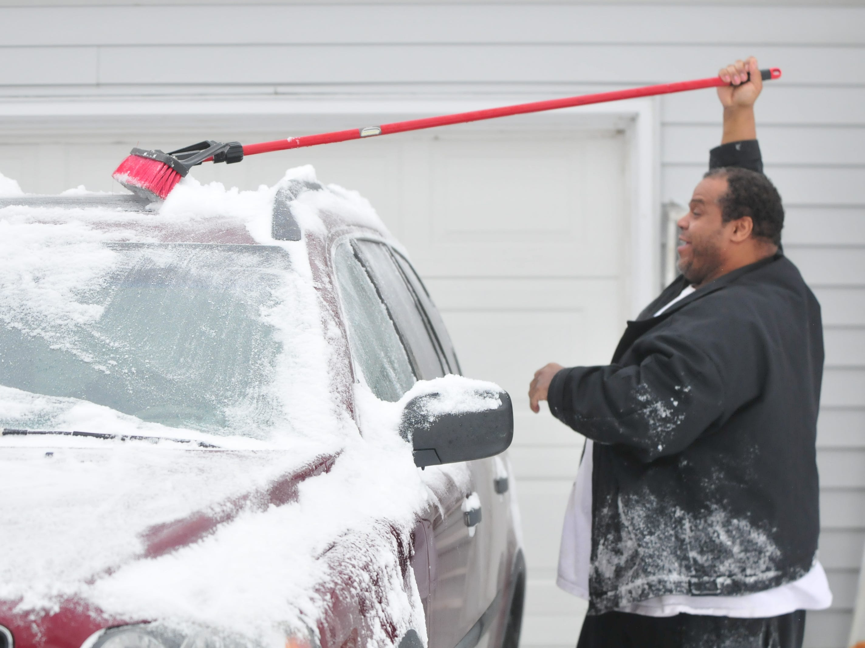 Frank Wilson clears a car Friday after an overnight snowstorm.