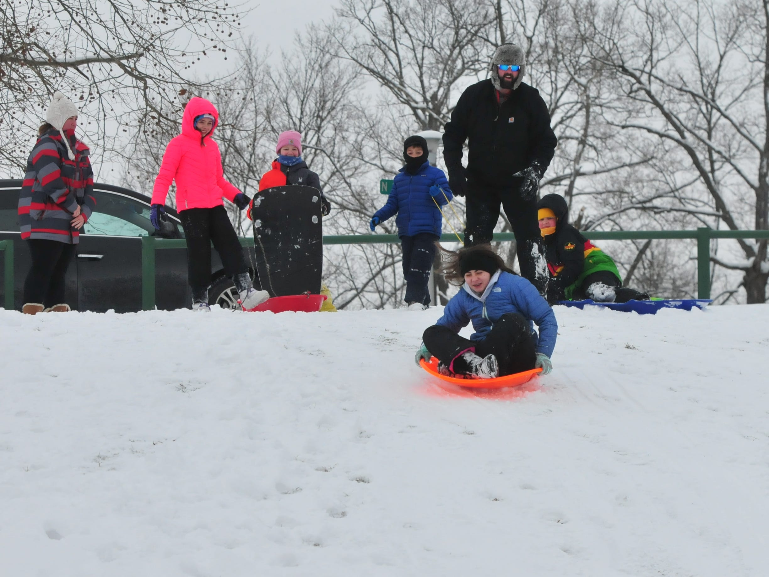 Josh Amyx gives Alyssa Amyx a push as others watch Friday at Roosevelt Hill in Glen Miller Park.