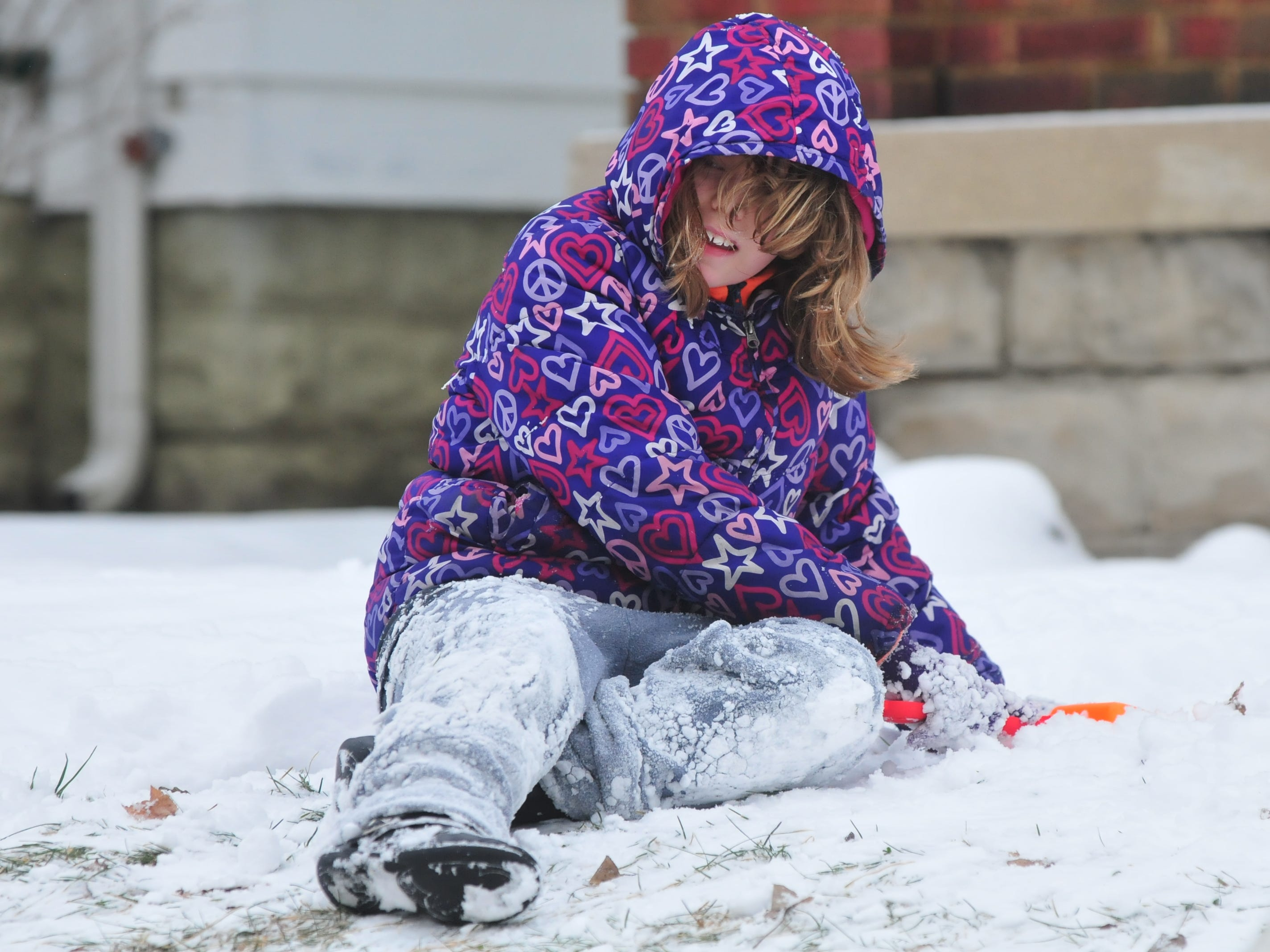 Kyla France plays in the snow Friday. She was outside with her aunt Laurie Wilson and her cousin Miah France.