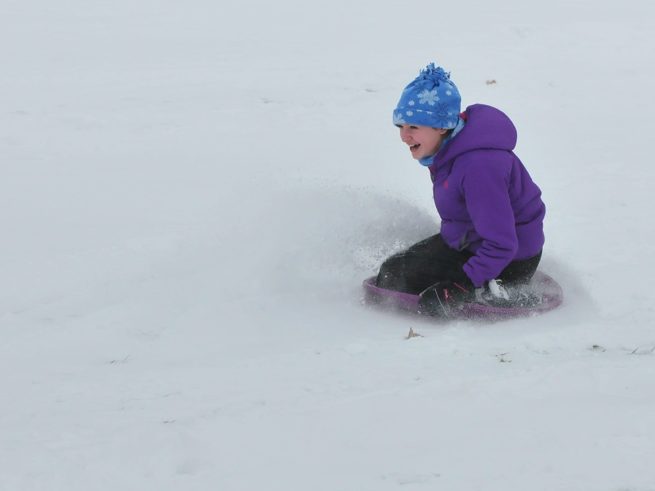 Julie Carter sleds Friday at Roosevelt Hill in Glen Miller Park.