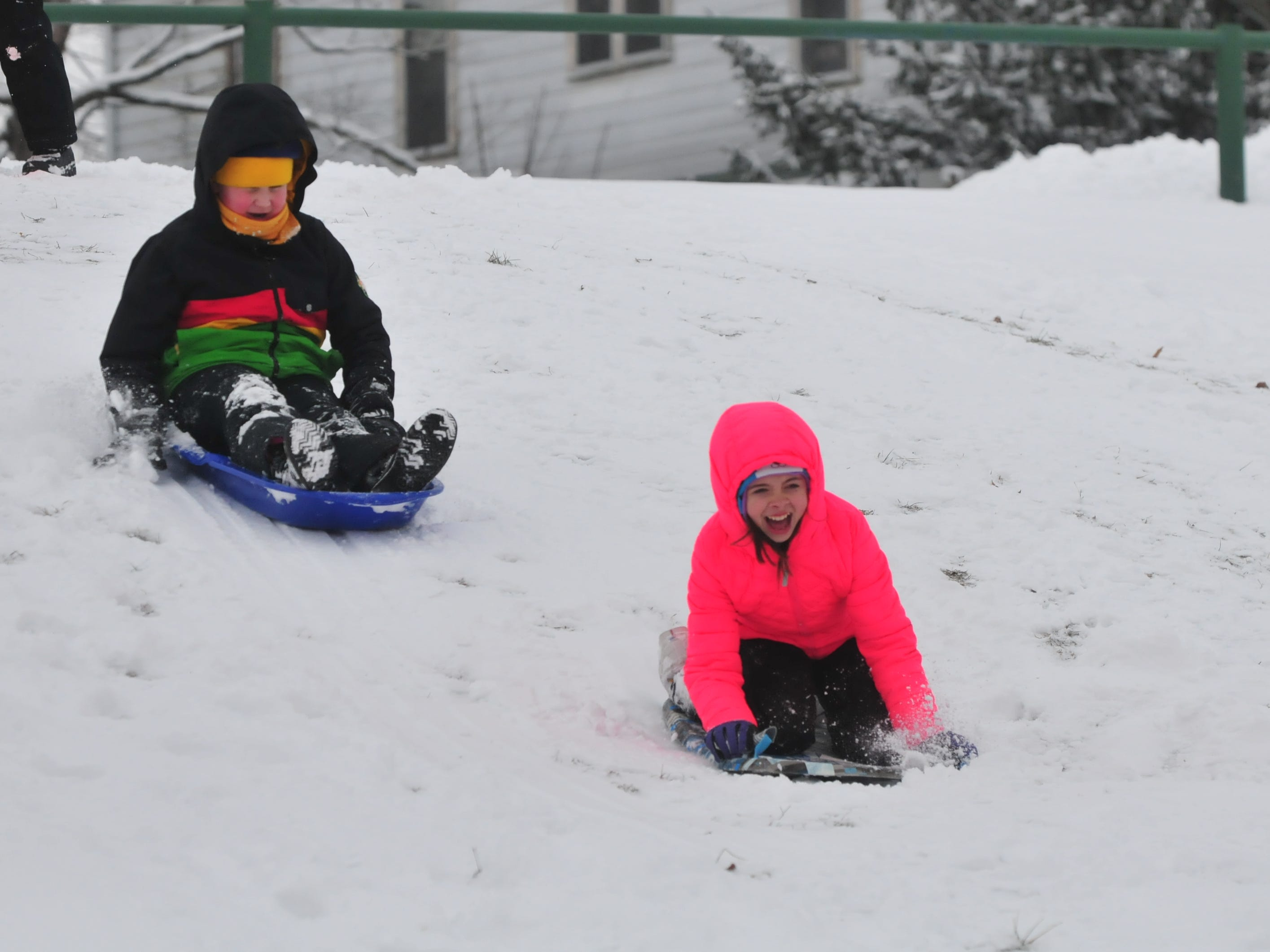 Addison Amyx and Gavin Belanga sled Friday at Roosevelt Hill in Glen Miller Park.