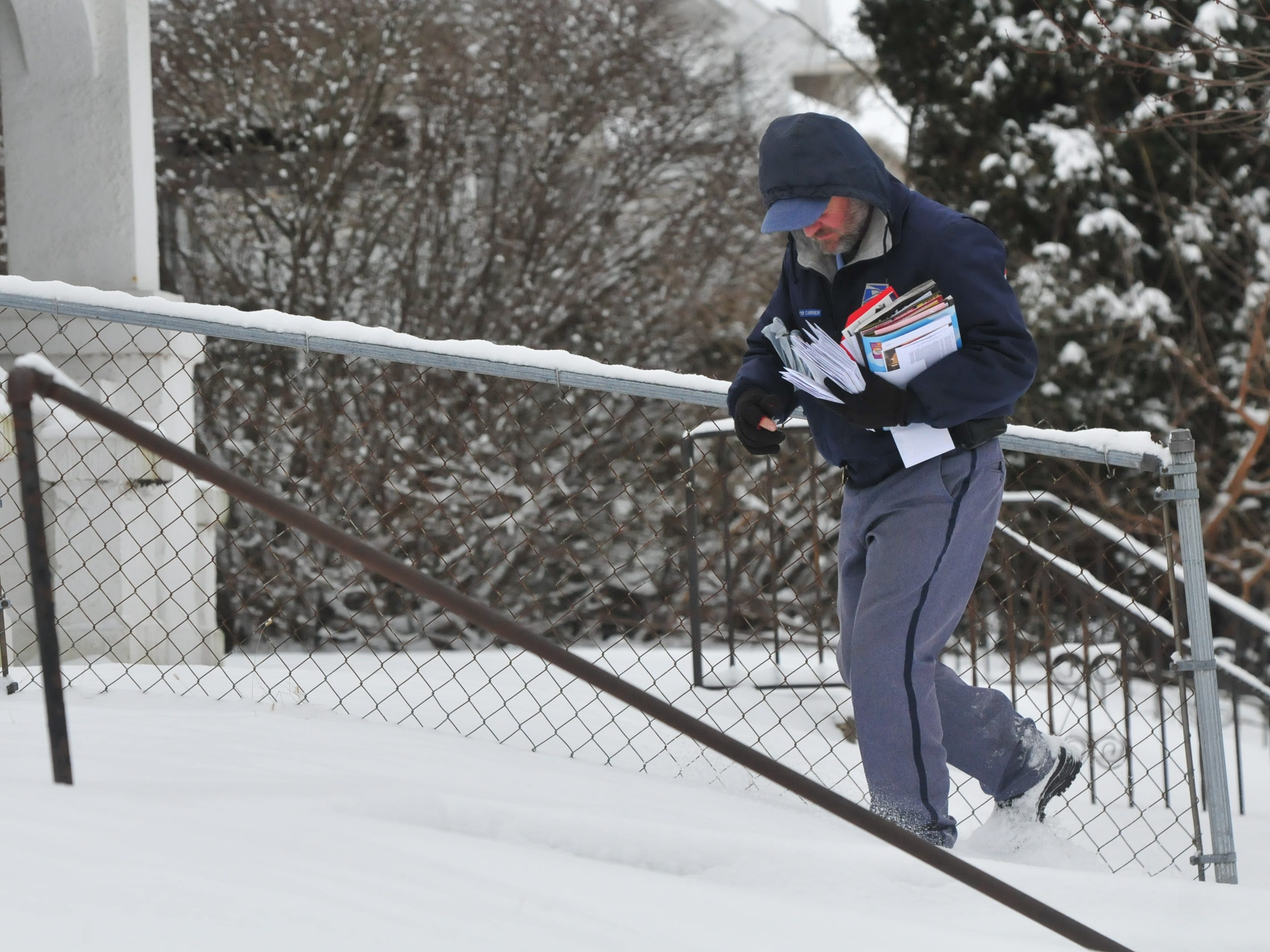 After two days without mail delivery because of dangerous cold, mail carriers were back on their routes Friday despite the overnight snowstorm.