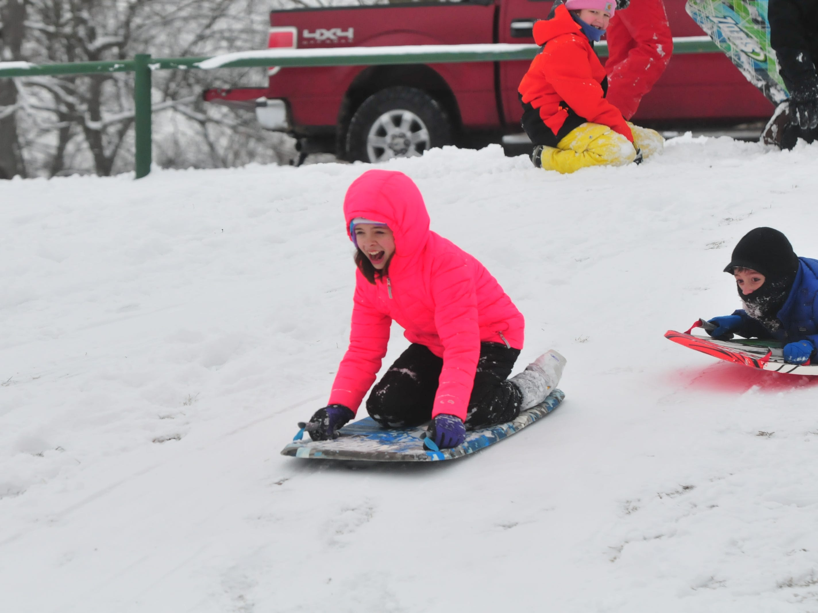 Addison Amyx and Tyler Amyx sled Friday at Roosevelt Hill in Glen Miller Park.