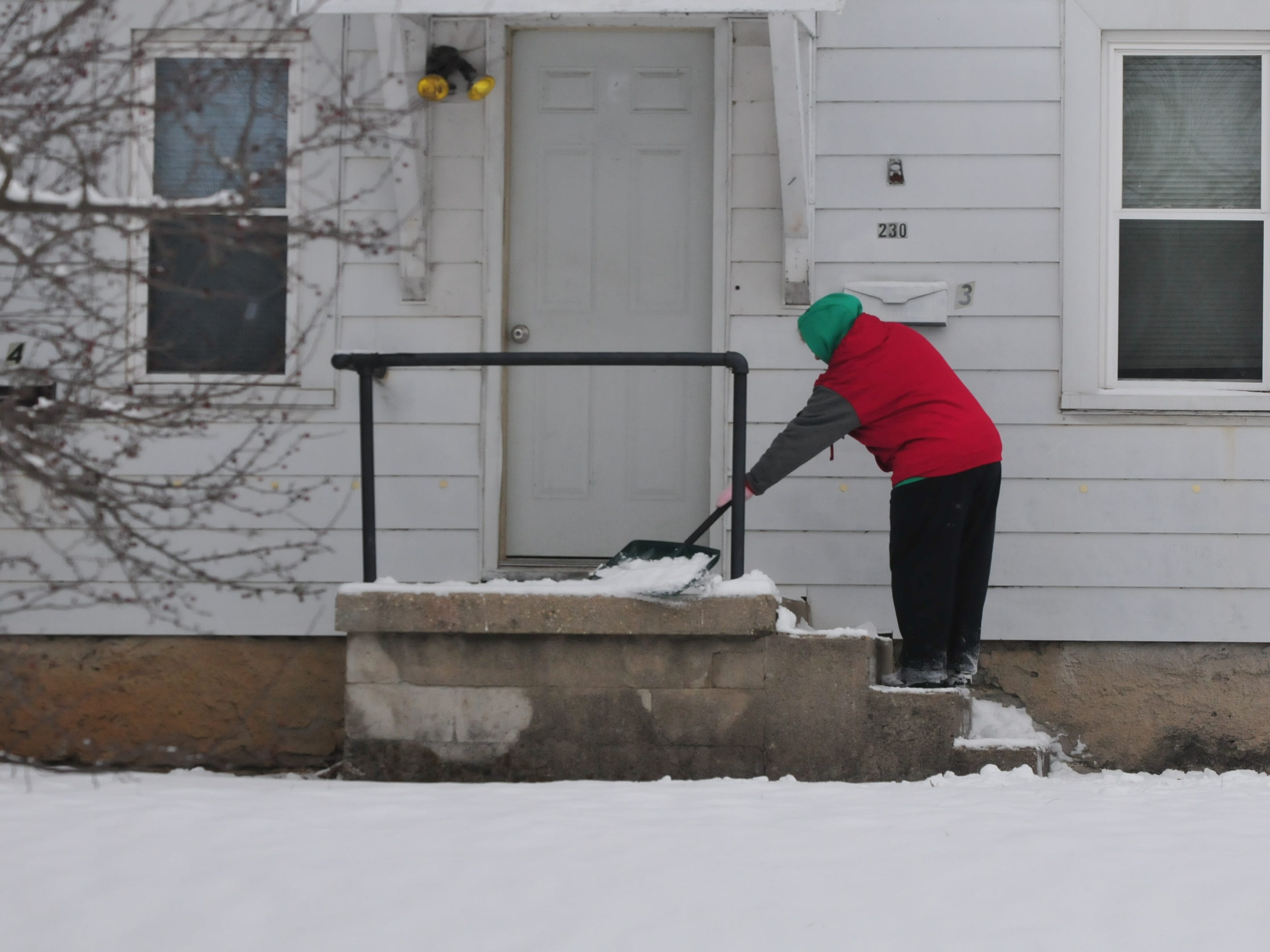 Laurie Wilson shovels snow from a stoop Friday.