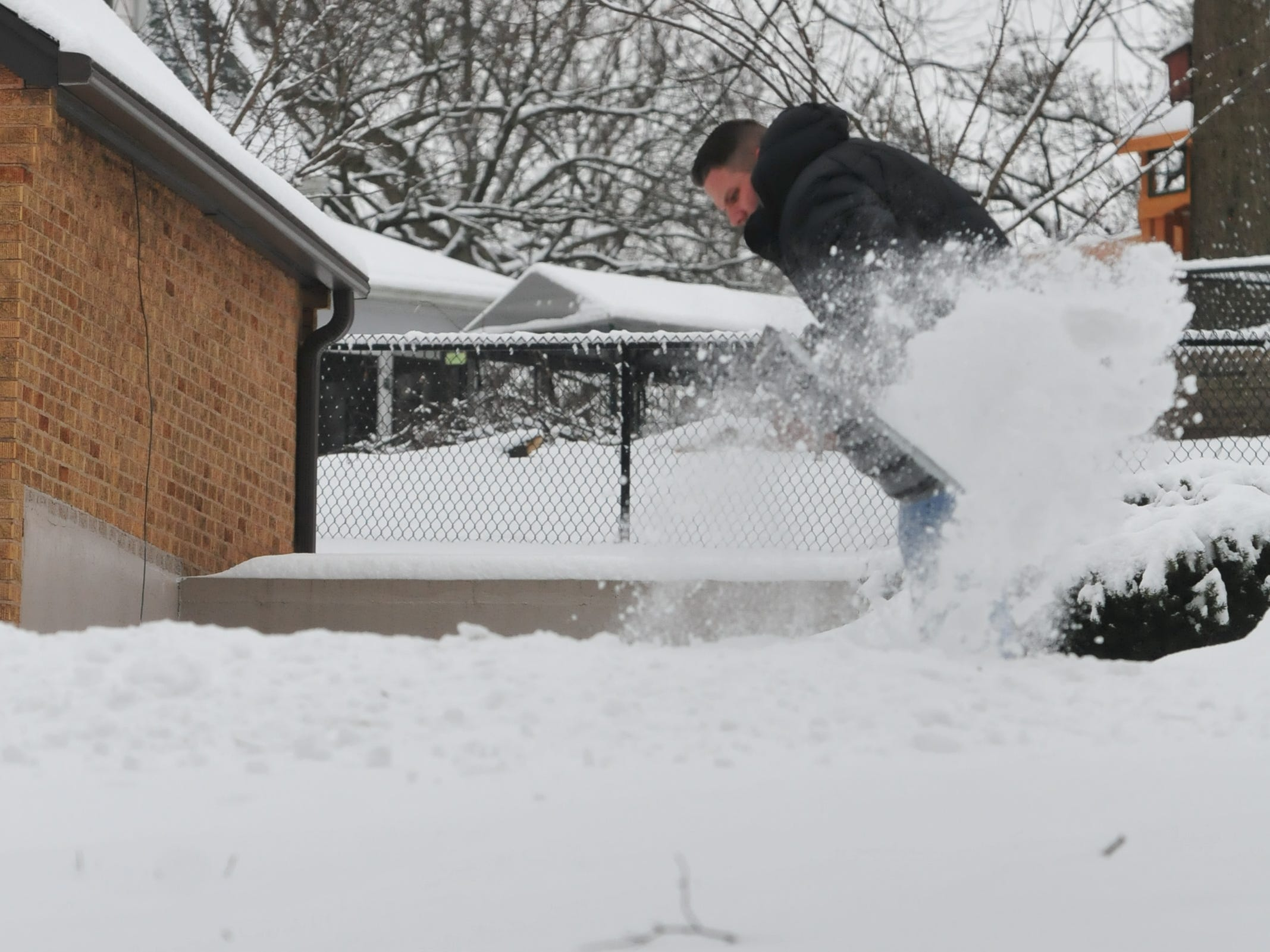 Elijah Barker shovels a driveway Friday after an overnight snow.
