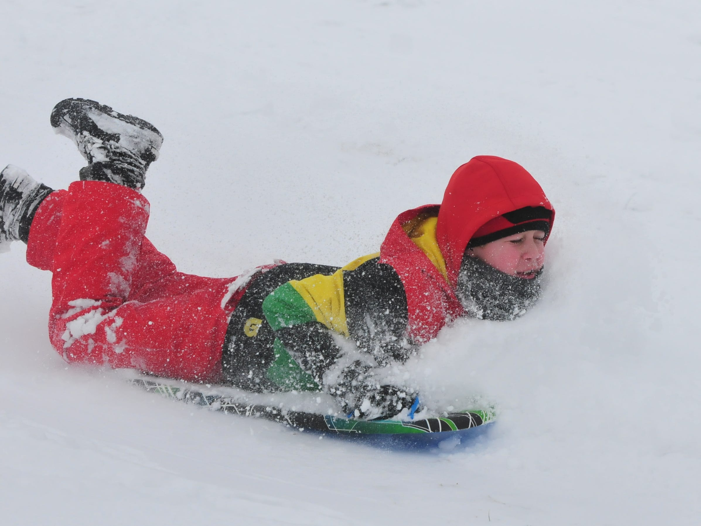 Logan Belanga sleds Friday at Roosevelt Hill in Glen Miller Park.