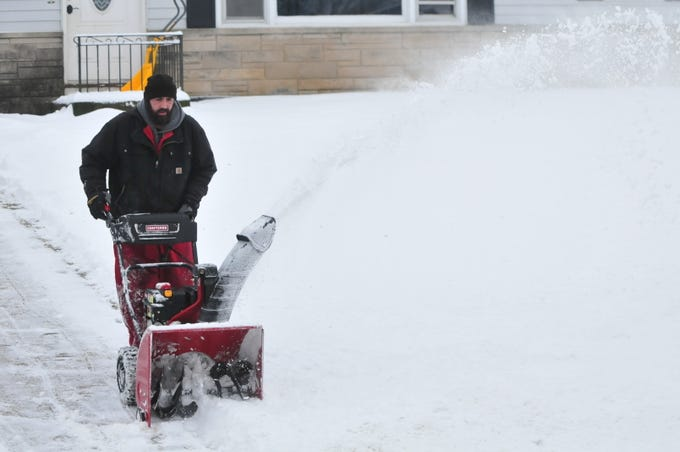 Jeffrey Lamberson helps a neighbor by clearing a driveway Friday after an overnight snowstorm.