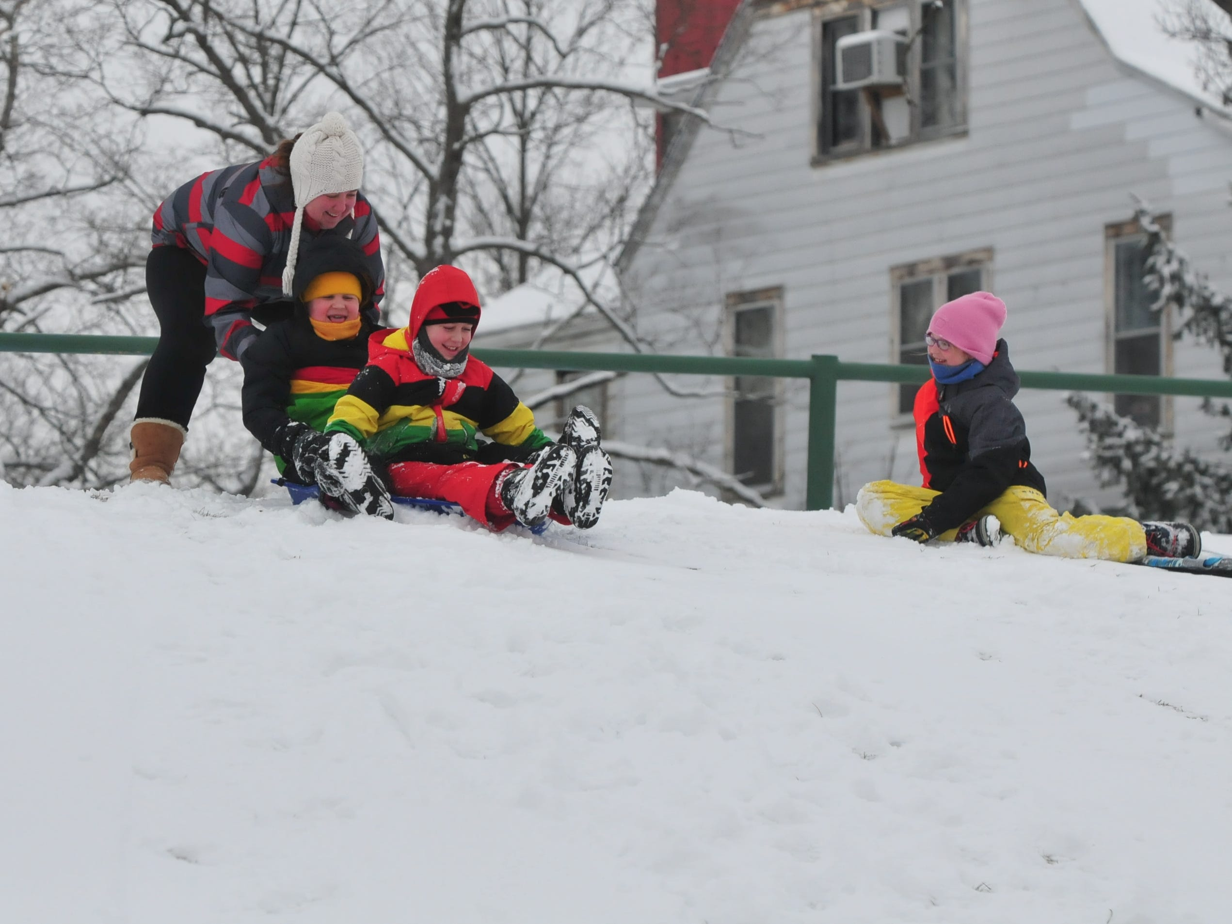 Katie Belanga gives a push to Gavin Belanga and Logan Belanga as Addie Belanga watches Friday at Roosevelt Hill in Glen Miller Park.