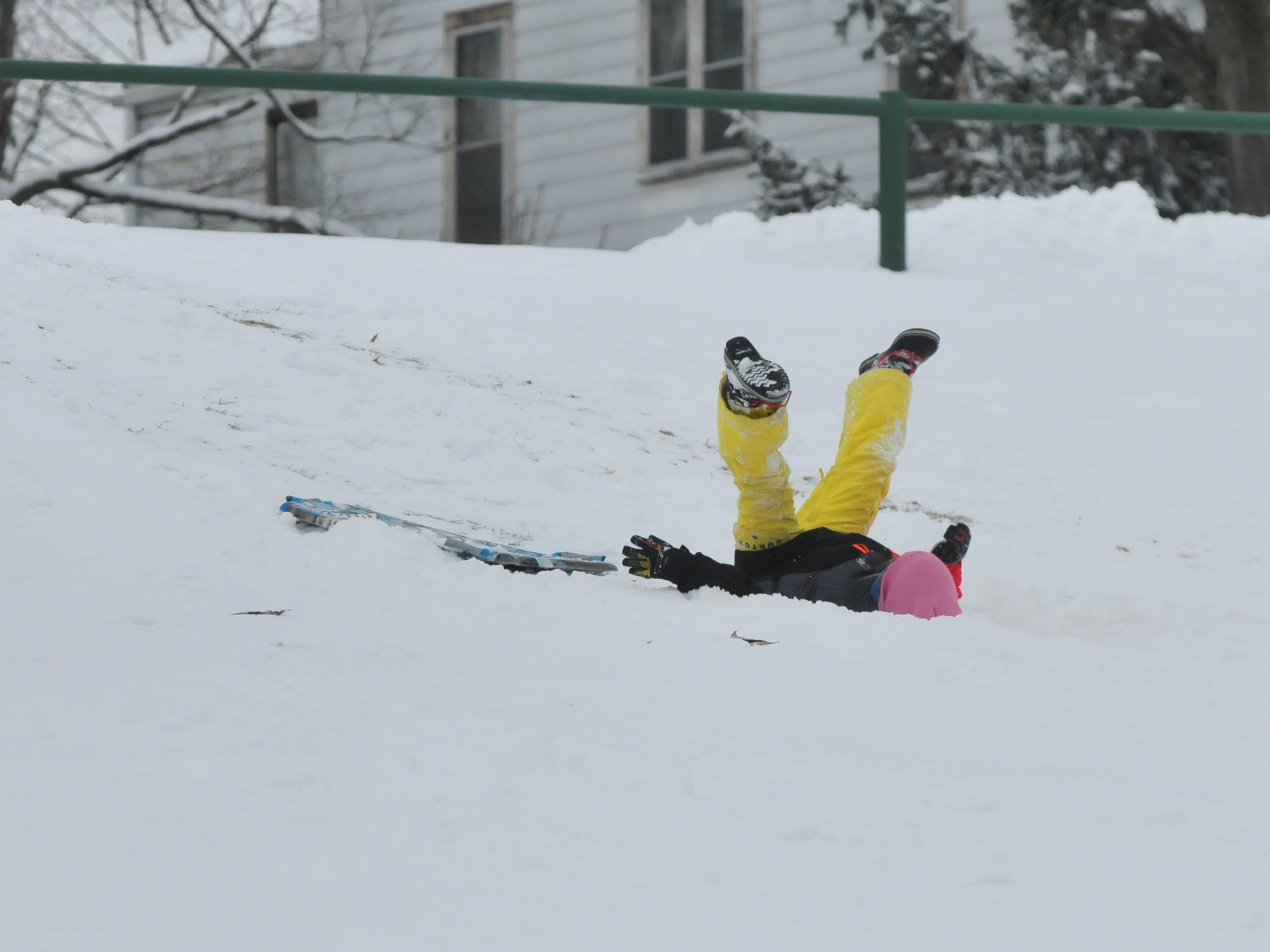 Addie Belanga falls into the snow Friday while using a sled like a snowboard at Roosevelt Hill in Glen Miller Park.