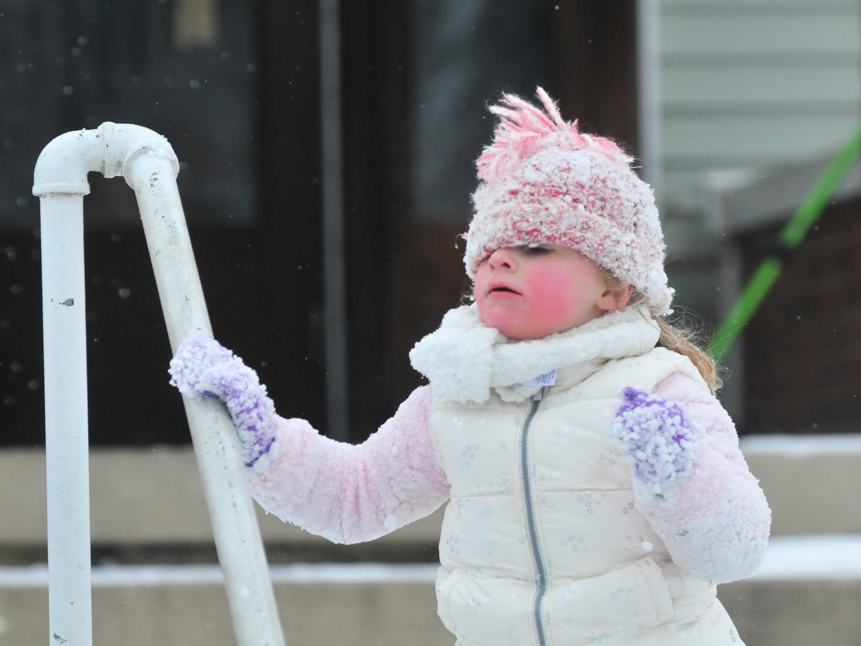 Miah France peers from beneath a snow-covered hat Friday. She was outside with her mom, Laurie Wilson, and cousin Kyla France.