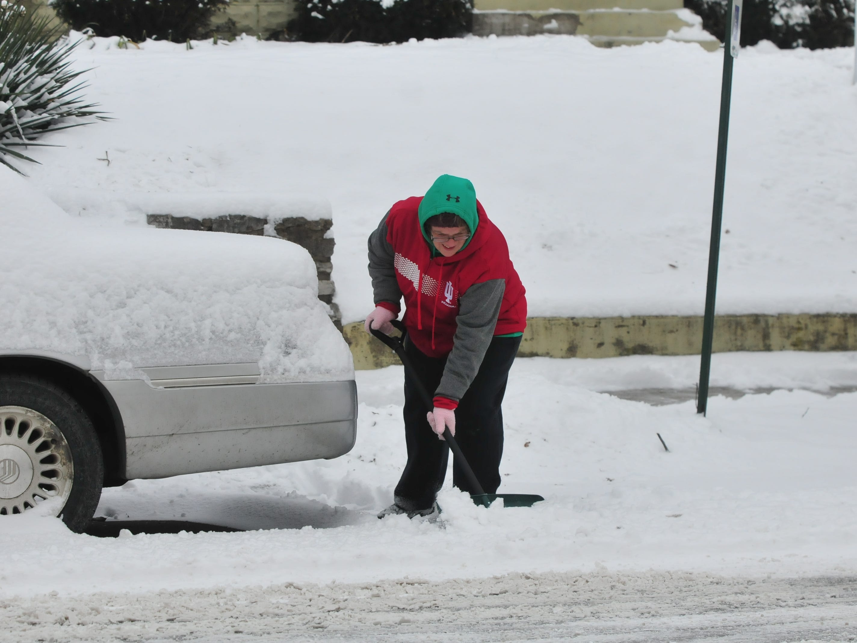 Laurie Wilson shovels snow away from a car Friday.