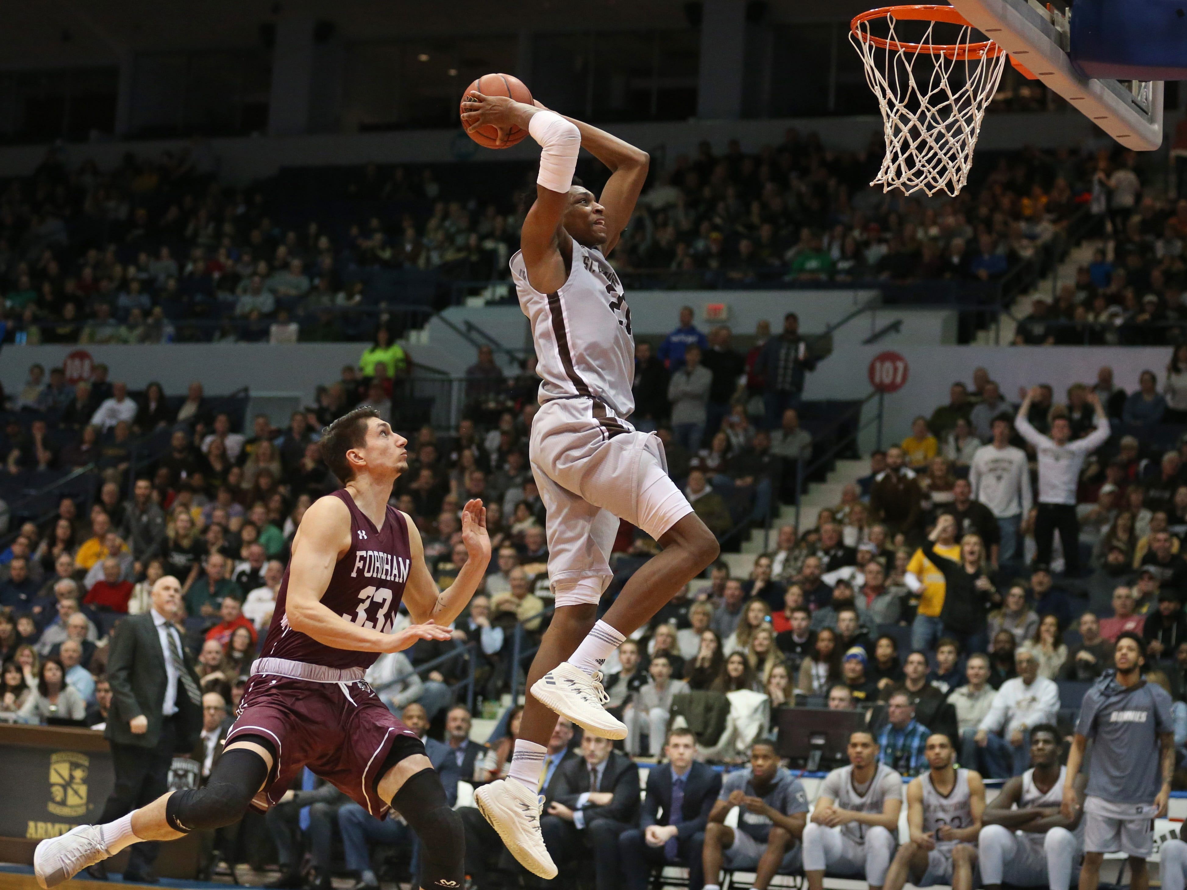 THE PHOTO: St. Bonaventure's Osun Osunniyi slams home the final two points of the game as he outraces Fordham's David Pekarek to the basket during their game at the Blue Cross Arena in Rochester Saturday, Jan. 12.  The Bonnies won the game 71-44. FROM SHAWN: What a great event to cover! Of all the dunk pictures I made during the game, this one was my favorite.  I love how both Bonnies players on the bench and fans in the stands are starting to rise up to celebrate as Osunniyi slams in the final points of the game.  This side angle to the basket really helps show the venue and crowd, and give more of a feeling for the atmosphere in the area that you don't get with a super tight action photo of a dunk.