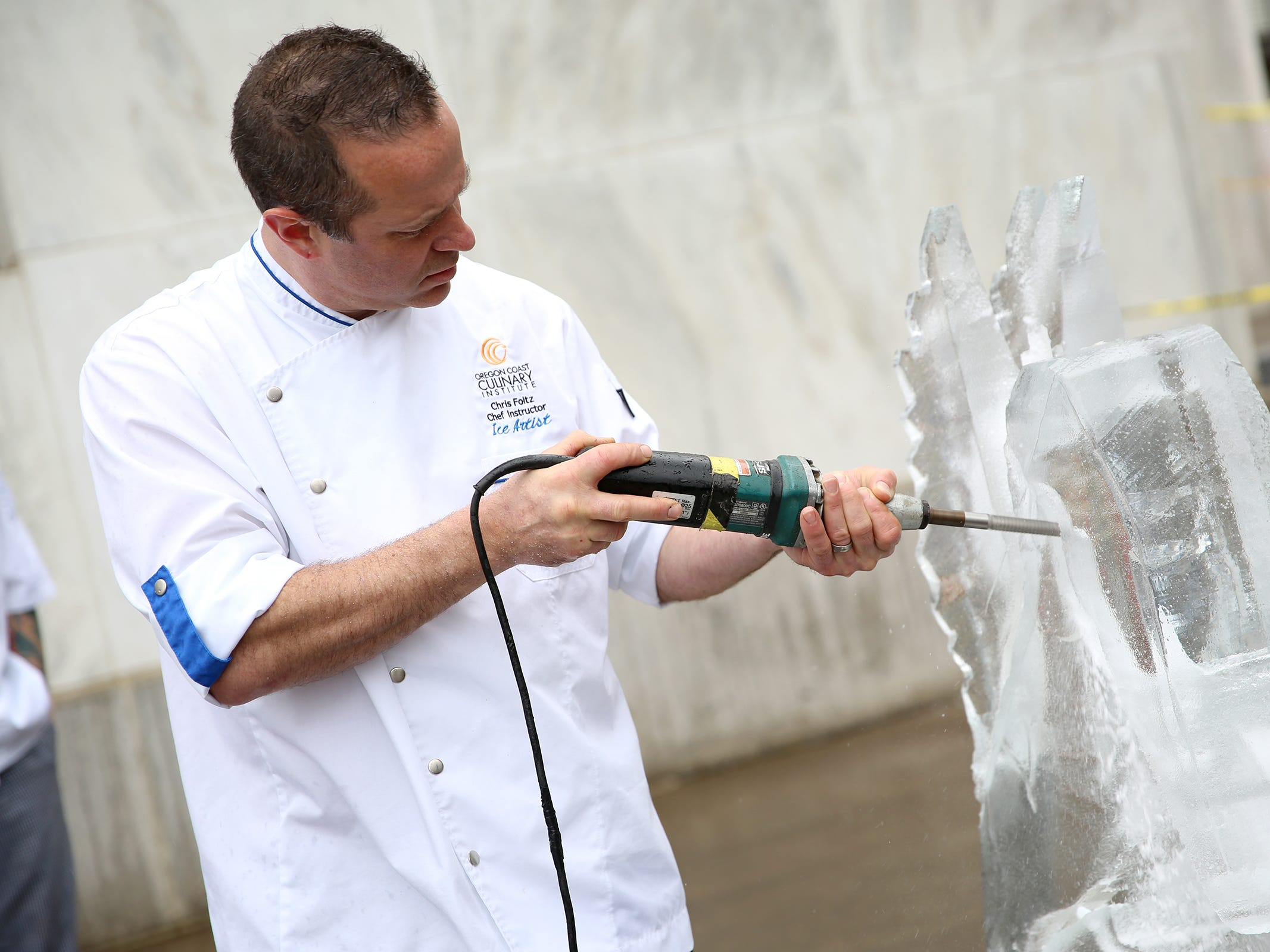 Chef Chris Foltz, an ice sculpture and instructor at Southwestern Community College's culinary program, works on a sculpture during Career and Technical Education (CTE) day at the Oregon State Capitol in Salem on Friday, Feb. 1, 2019.