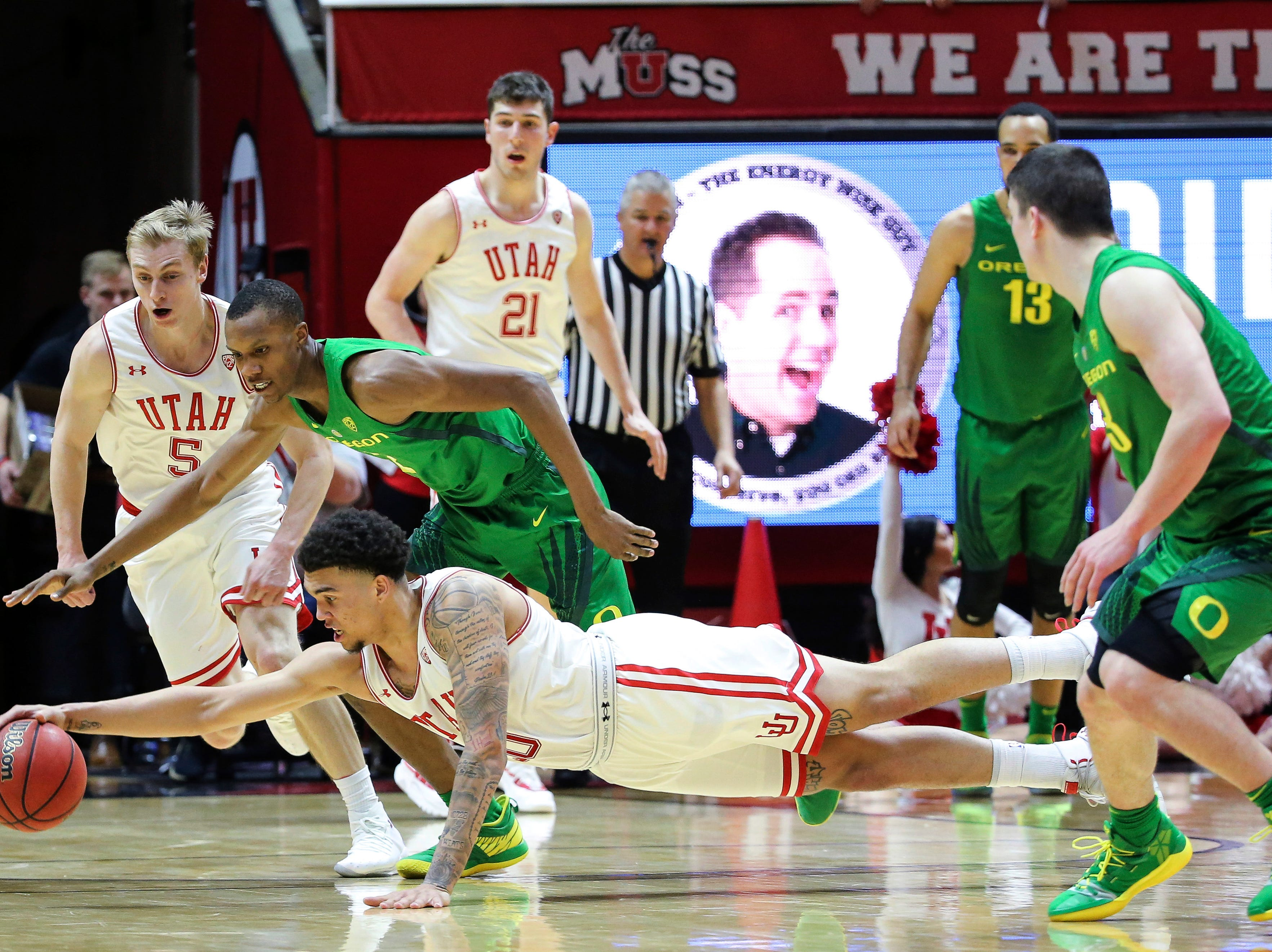 Utah forward Timmy Allen (20) dives in front of Oregon forward Louis King (2) to grab the ball during the second half of an NCAA college basketball game Thursday, Jan. 31, 2019, in Salt Lake City. Oregon won 78-72.