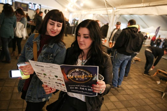 Odessa Engstom (left) and Casey Sunshine look over a beer selection map at Salem Winter Brewfest in downtown Salem near the Oregon State Capitol on Jan. 29, 2019.