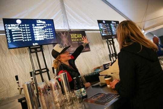 Andria Downard points out the beer selection at Salem Winter Brewfest in downtown Salem on Thursday, Jan. 31, 2019.
