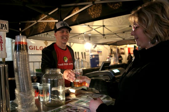 Damian Cooper serves a Lagunitas mango based ale to a customer at Salem Winter Brewfest in downtown Salem in front of the Oregon State Capitol on Thursday, Jan. 31, 2019.