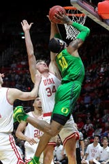 Oregon forward Kenny Wooten (14) jumps past Utah center Jayce Johnson (34) and shoots the ball during the first half of an NCAA college basketball game Thursday, Jan. 31, 2019, in Salt Lake City.