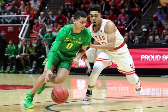 Oregon guard Will Richardson (0) dribbles the ball past Utah guard Sedrick Barefield (2) during the first half of an NCAA college basketball game Thursday, Jan. 31, 2019, in Salt Lake City.
