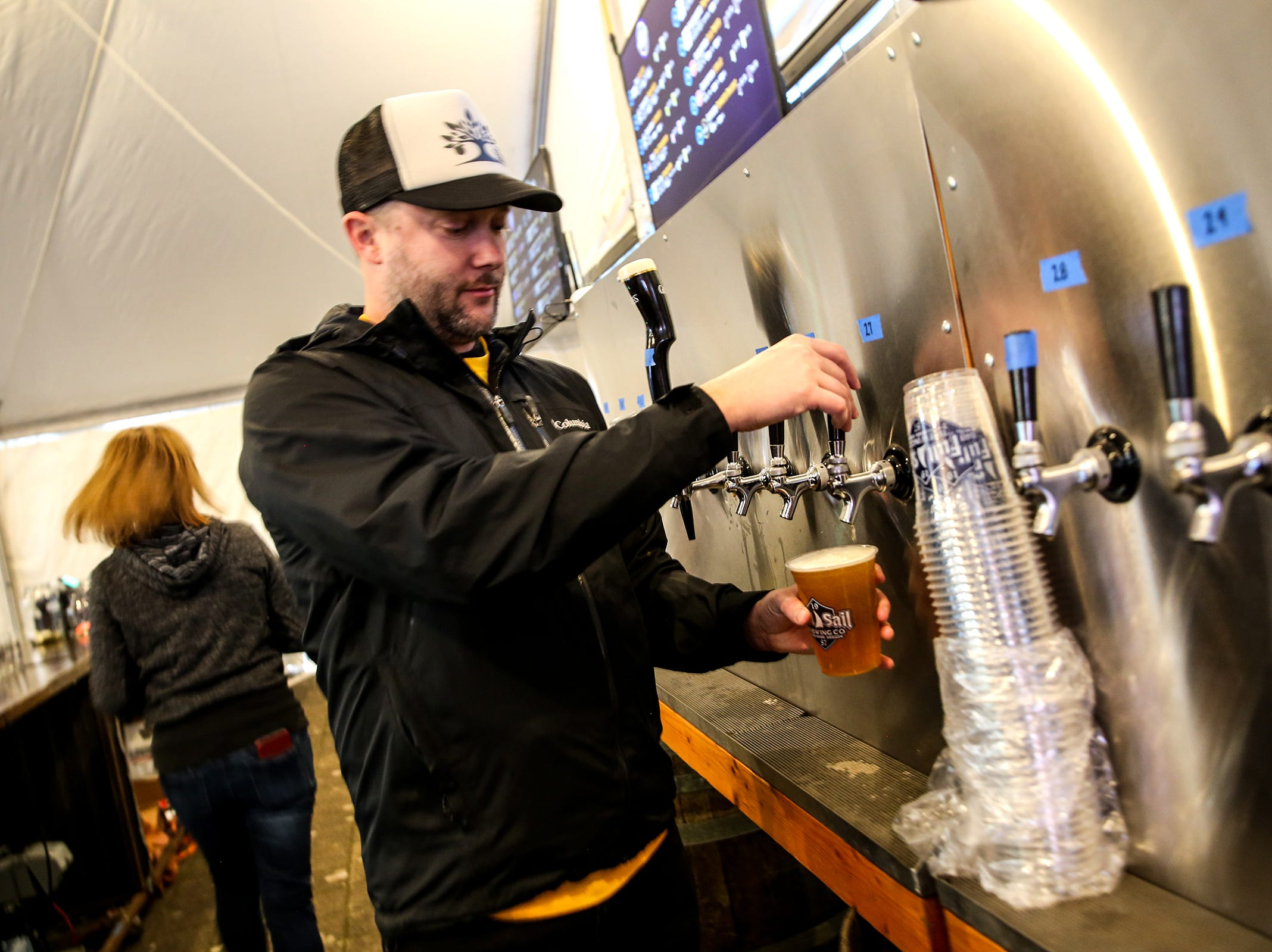 Josian Phillaps pours a beer at Salem Winter Brewfest in downtown Salem in front of the Oregon State Capitol on Thursday, Jan. 31, 2019.