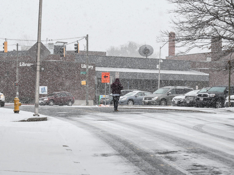 A woman walks through the snow on E. Main Street in downtown Salisbury on Friday, Feb. 1, 2019.