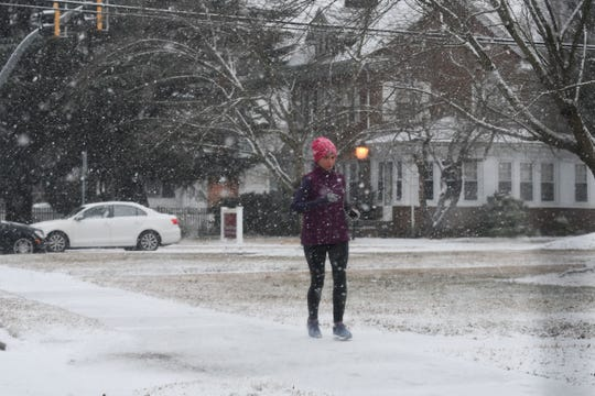 A woman takes a run through snowy weather.
