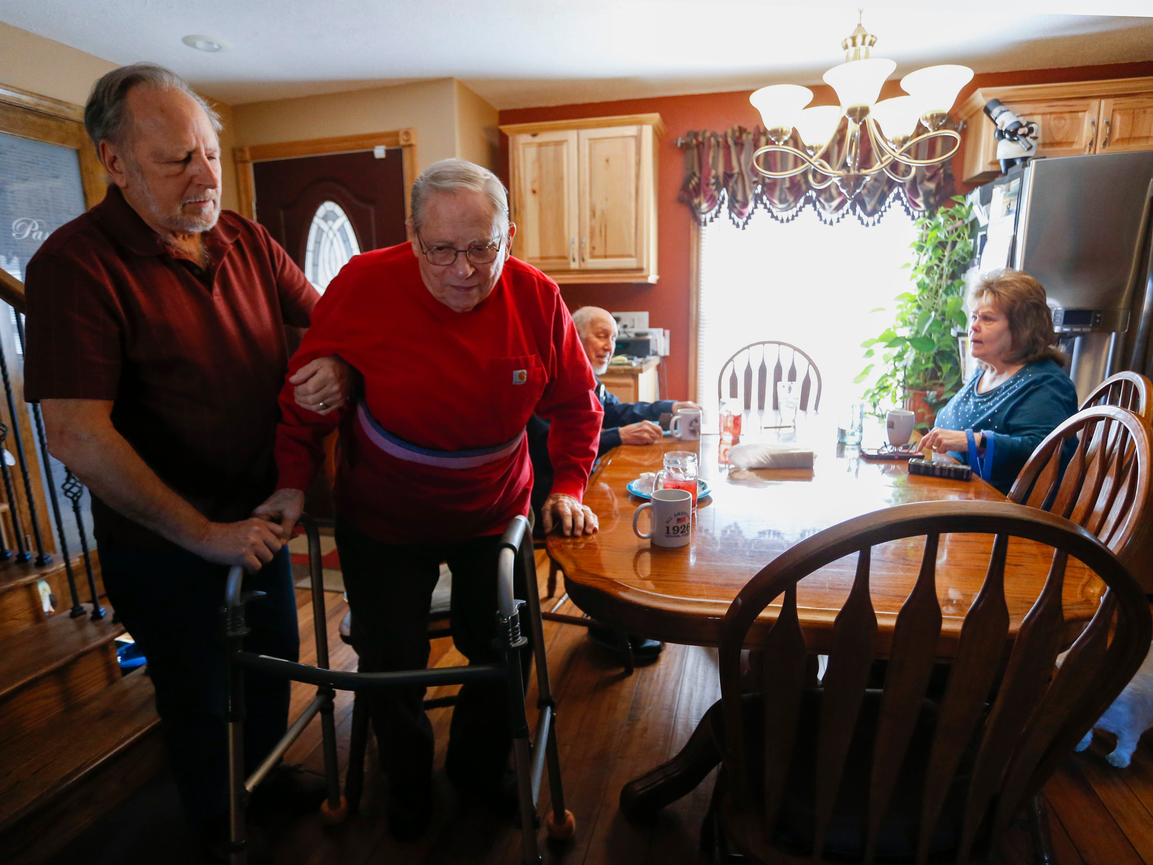 Frank Keim helps veteran Donald Gundlach, 92, up from his chair on Tuesday, Jan. 29, 2019. Keim and his wife opened up their home to veterans as part of the VA's Medical Foster Home Program.