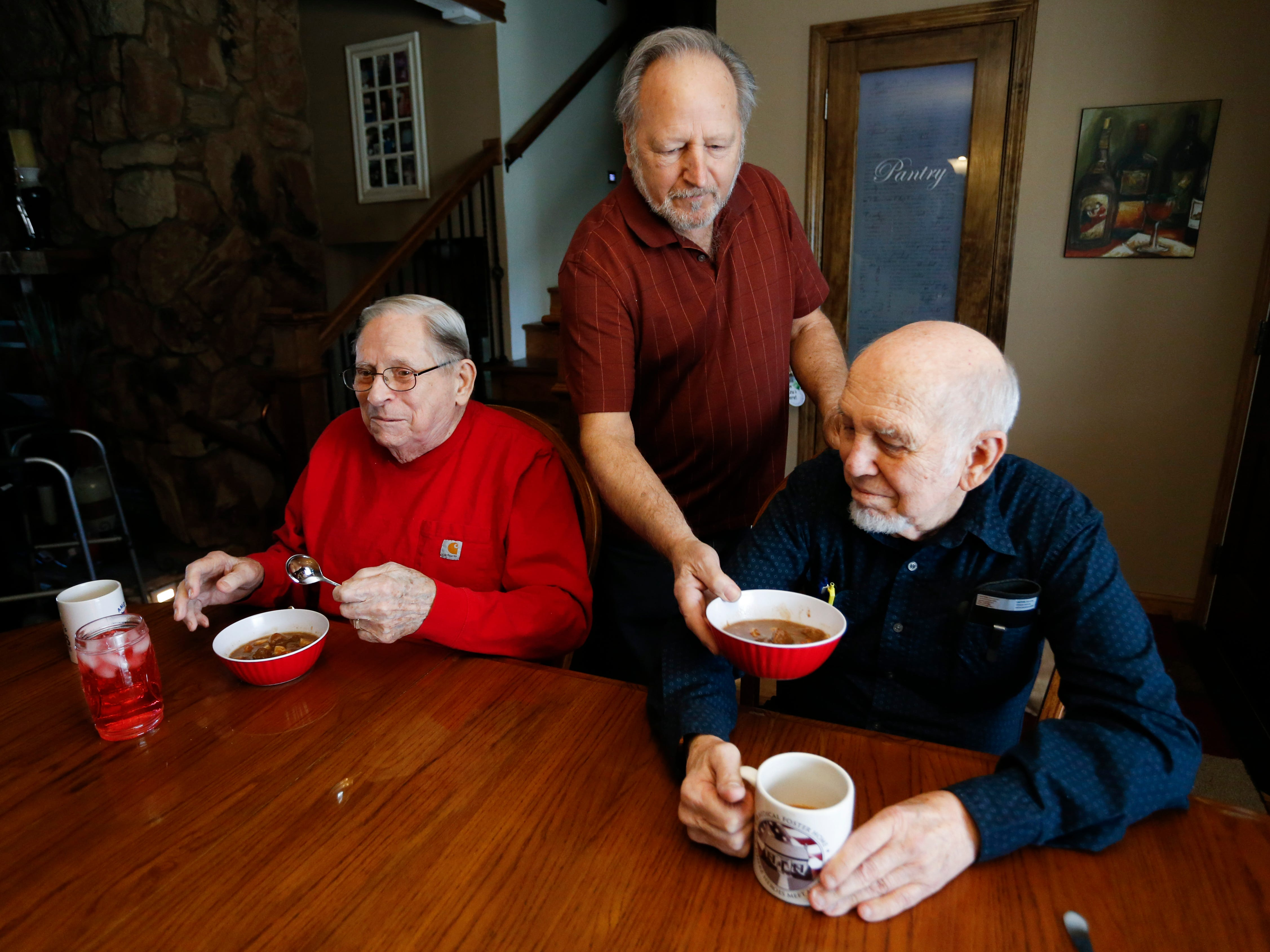 Frank Keim brings a bowl of stew to veterans Donald Gundlach (left), 92, and Gene Solomon, 77, on Tuesday, Jan. 29, 2019. Keim and his wife opened up their home to veterans as part of the VA's Medical Foster Home Program.