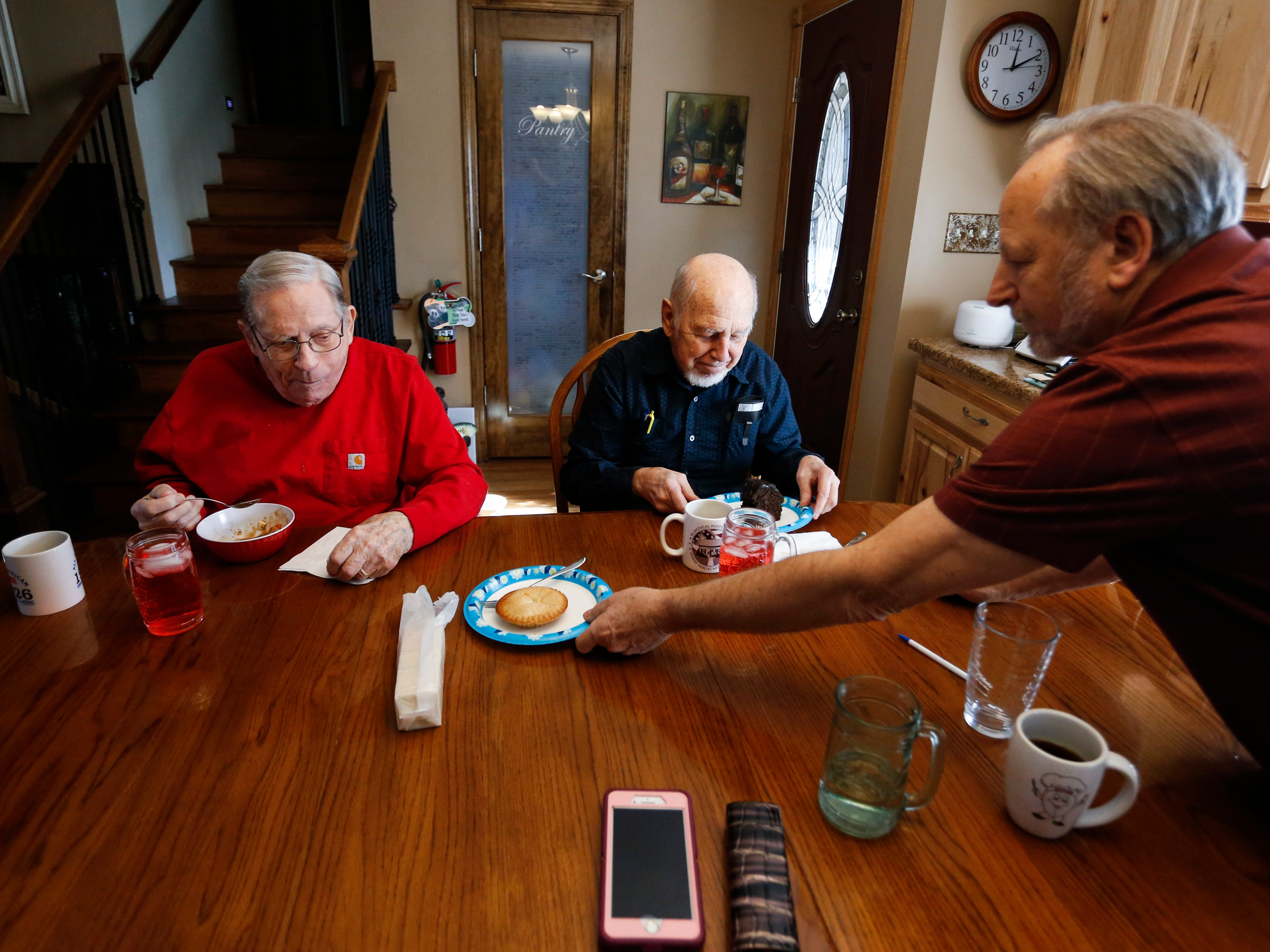 Frank Keim brings dessert to veterans Donald Gundlach (left), 92, and Gene Solomon, 77, on Tuesday, Jan. 29, 2019. Keim and his wife opened up their home to veterans as part of the VA's Medical Foster Home Program.