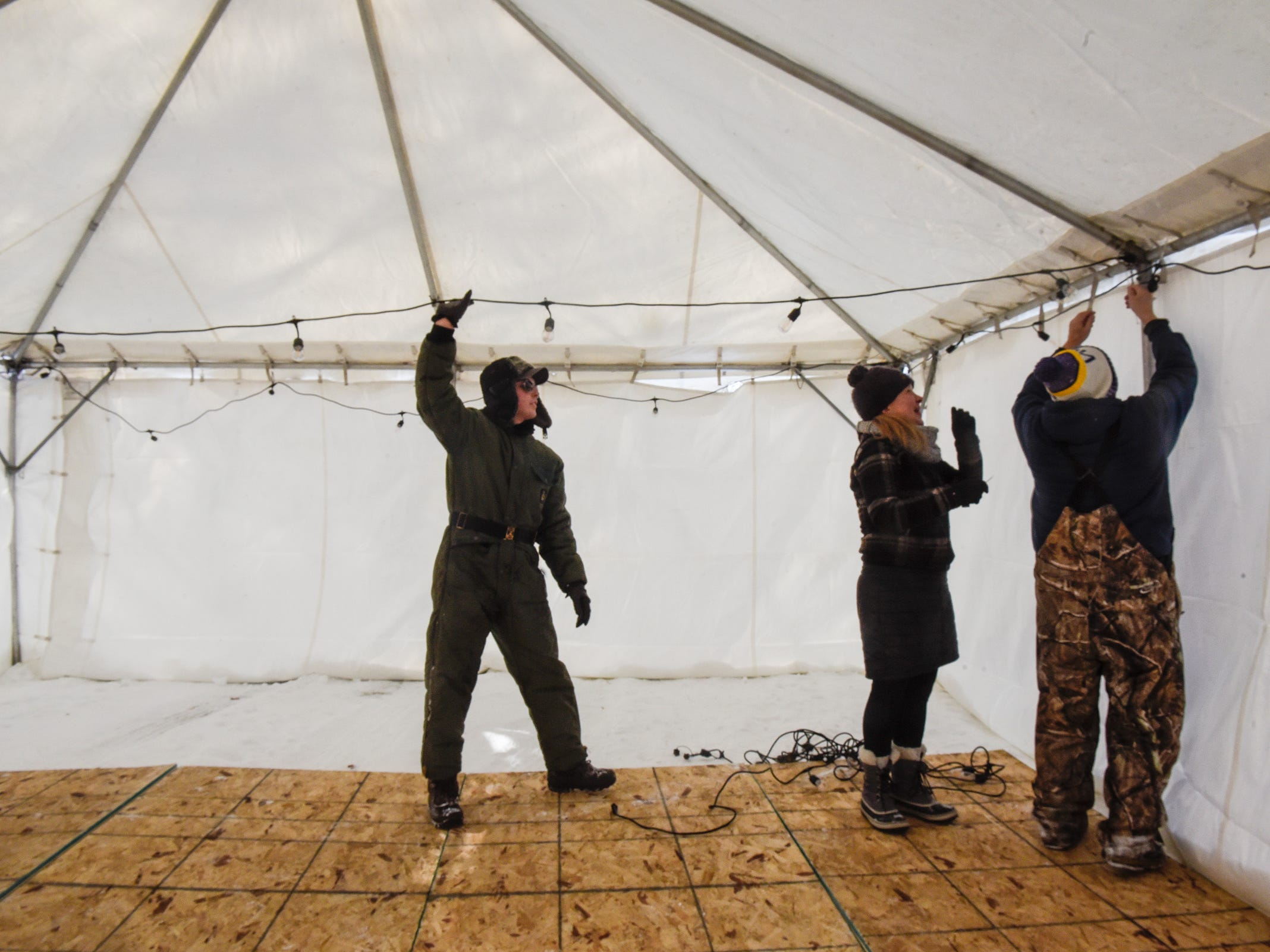 Volunteers string lights in a warming tent near the hockey rinks while preparing for the Granite City Outdoor Hockey Festival Friday, Feb. 1, at Blackberry Ridge Golf Club in Sartell.