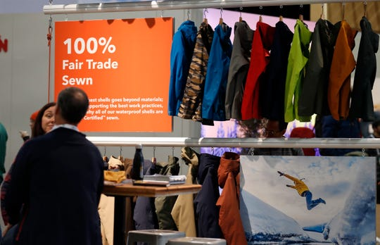 In this Wednesday, Jan. 30, 2019, photograph, a sign indicating items that were 100-percent fair trade-sewn marks a rack of jackets and shells in the Patagonia exhibit at the Outdoor Retailer & Snow Show in the Colorado Convention Center in Denver. Major players in the outdoor industry jumped into the political fight over national monuments two years ago and now have added climate change and sustainable manufacturing to their portfolio. (AP Photo/David Zalubowski)