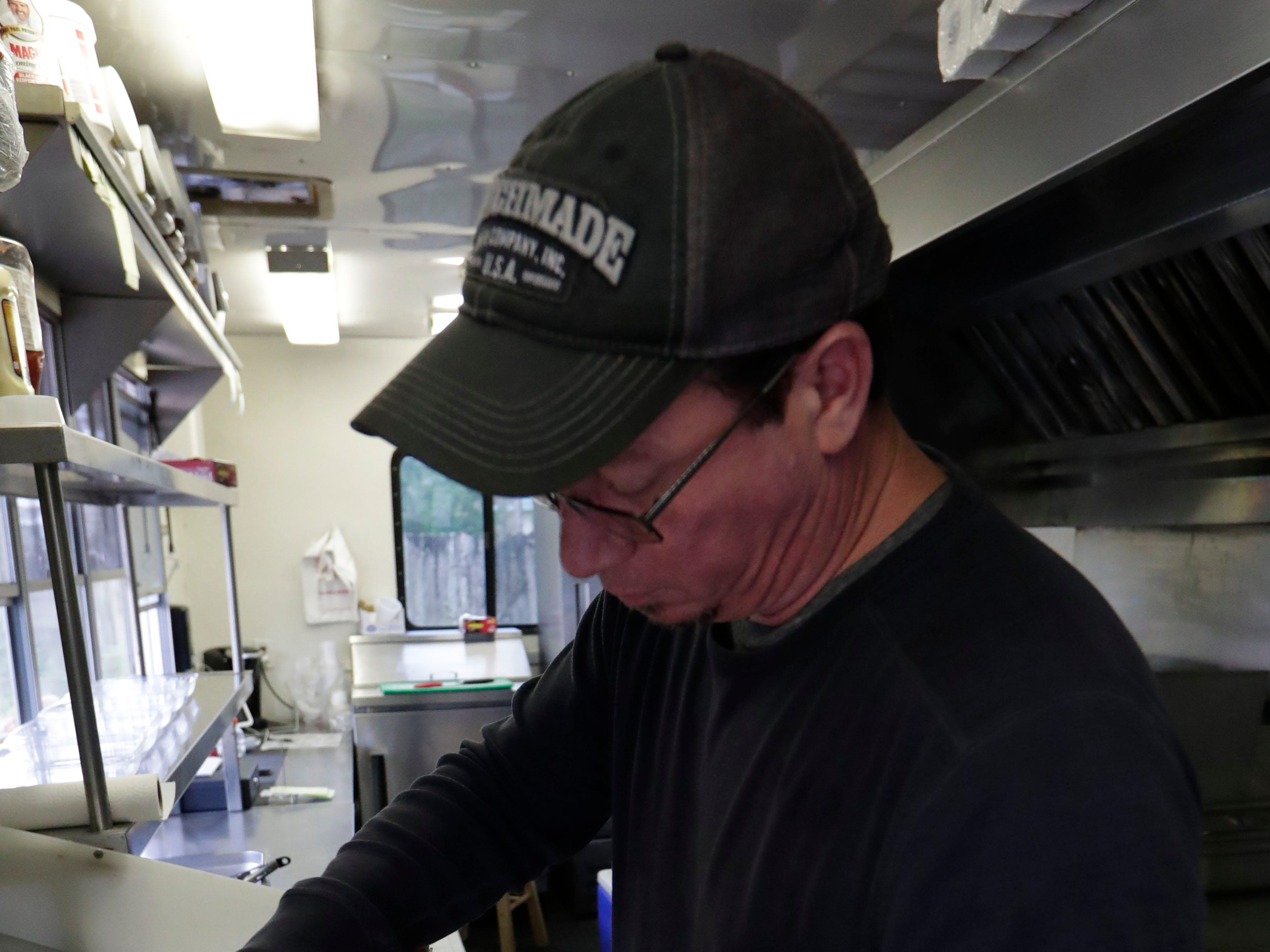 Ben Lovell, son of Leo Lovell who is the owner of Spring Creek Restaurant food truck located in Crawfordville, Fla., seasons shrimp before cooking them for a customer, Friday, Feb. 1, 2019.