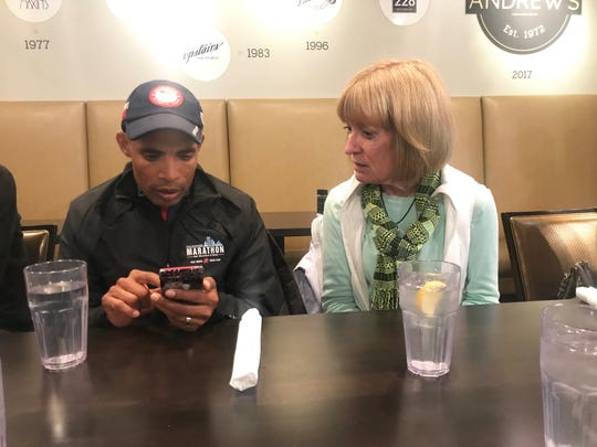 Olympic champion Meb Keflezighi looks through his phone to show a photo to Mary Jean Yon of Gulf Winds Track Club during a luncheon at Andrew's on Adams Street in Tallahassee on Friday, Feb. 1. Keflezighi is in town to compete in the Tallahassee Marathon festivities.