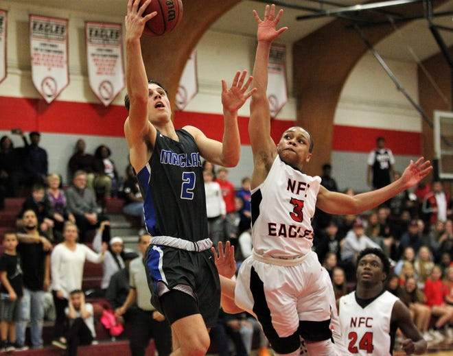 Maclay junior Ian Widener soars in for a layup before NFC junior Victor Clark can get there during the final minute of a game Thursday. Widener scored 15 points as the Marauders won 62-58.