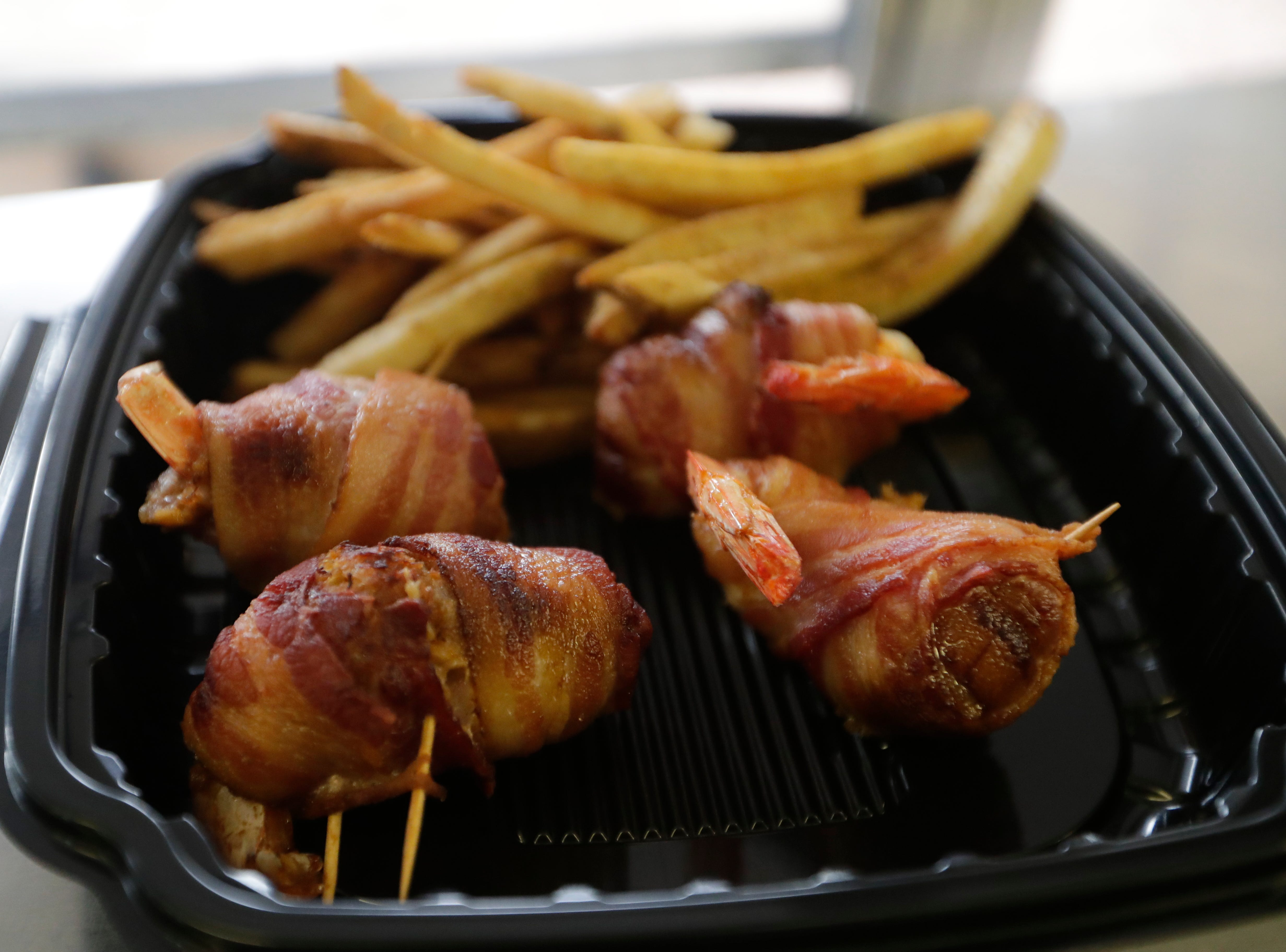 Fresh out of the fryer are bacon wrapped shrimp stuffed with crab, a family recipe, ready to be served to a customer at the Spring Creek Restaurant food truck in Crawfordville, Fla., Friday, Feb. 1, 2019.