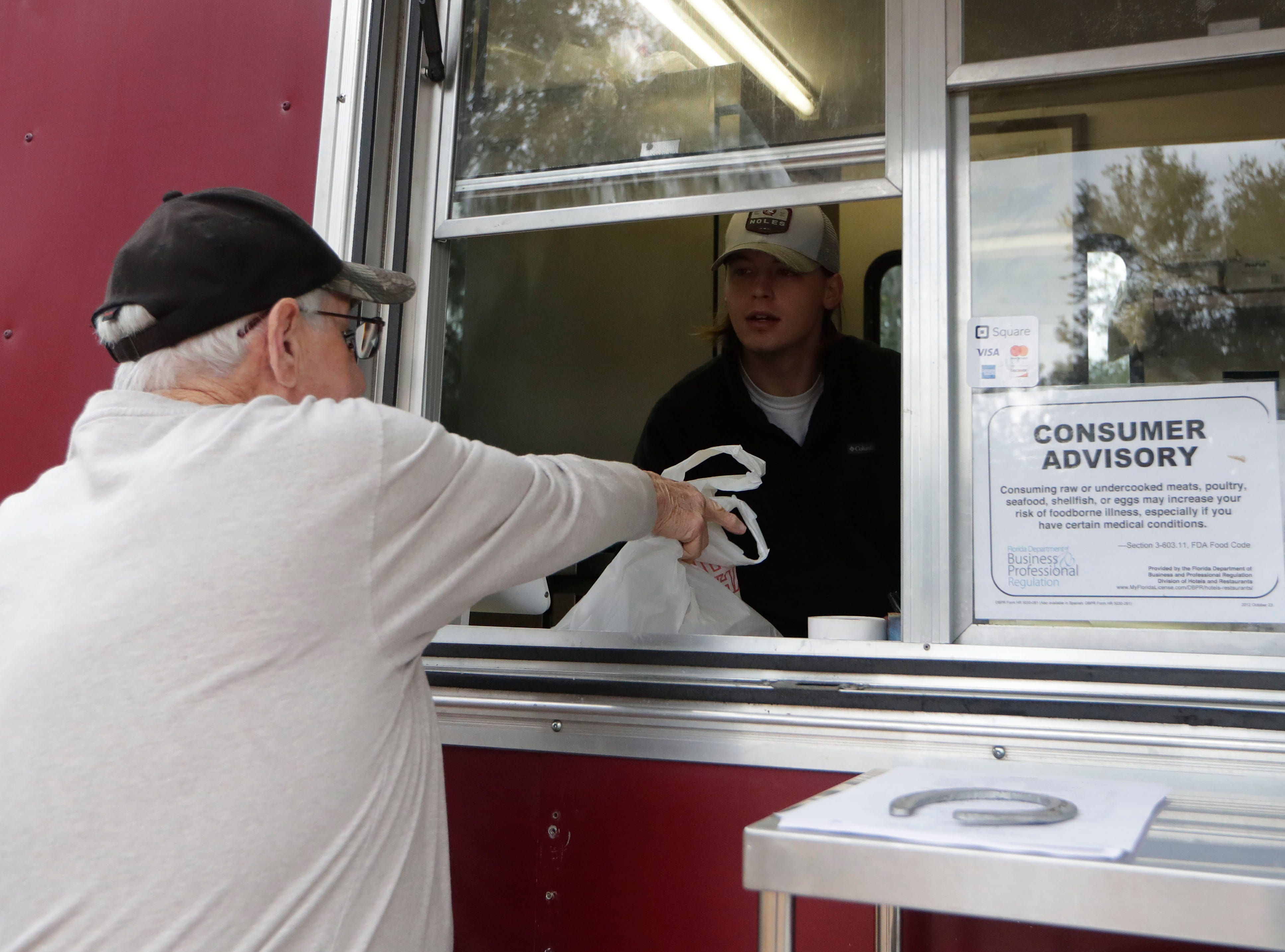 Preston Strickland picks up an order he placed over the phone at the Spring Creek Restaurant food truck in Crawfordville, Fla., Friday, Feb. 1, 2019.