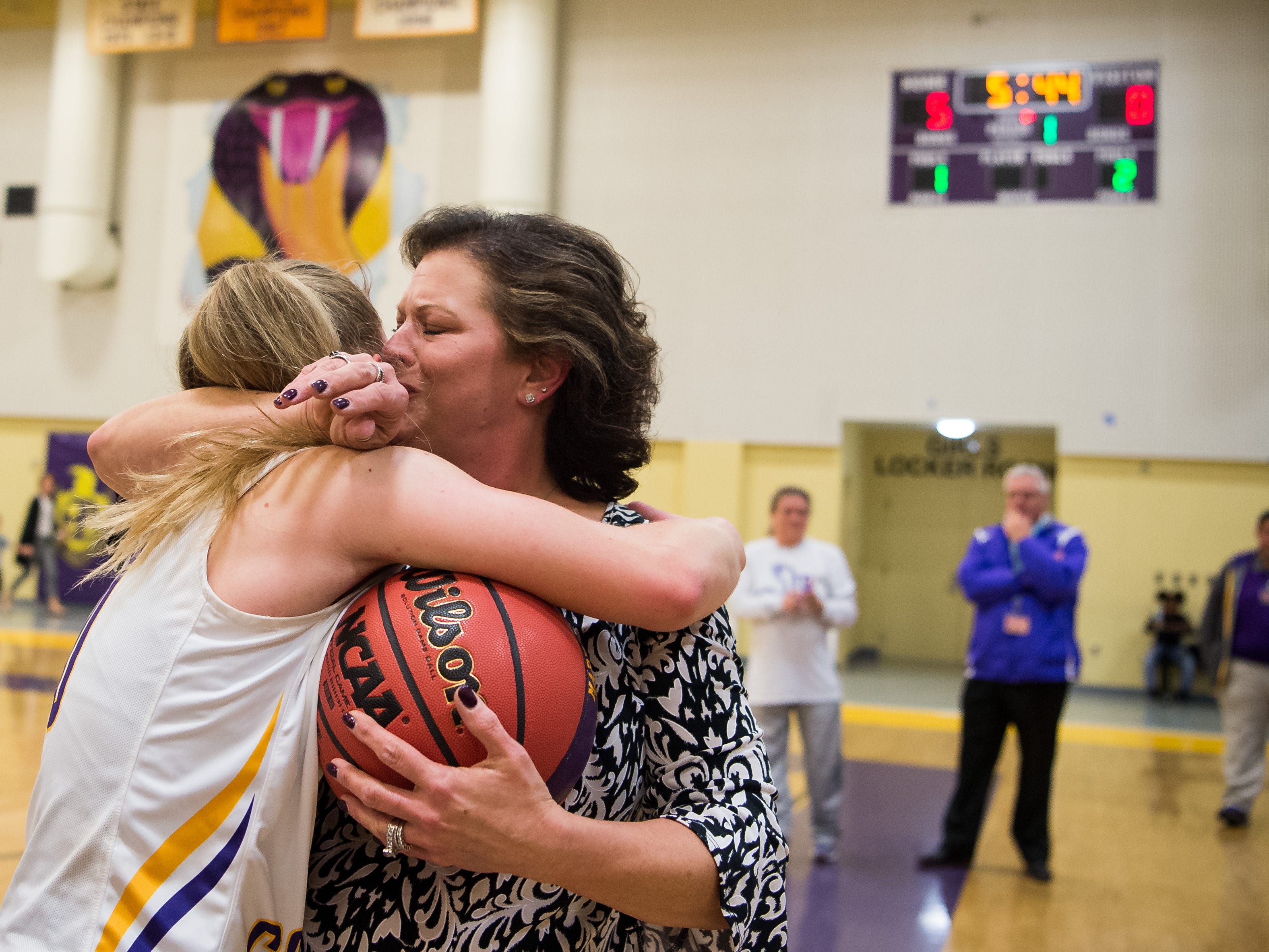 "Fort Pierce Central senior Maryanne Logsdon (left) is embraced by her mother, Stacy Logsdon, after scoring her 1,000th career point during their high school girls basketball game against Lake Worth on Thursday, Jan. 31, 2019, at Fort Pierce Central High School. ""We're very proud of her, she still continues to amaze us...her work ethic is unbelievable,"" the mother said, adding that Maryanne signed to play with Indian River State College after graduation. ""Our coach is amazing, she's family."""