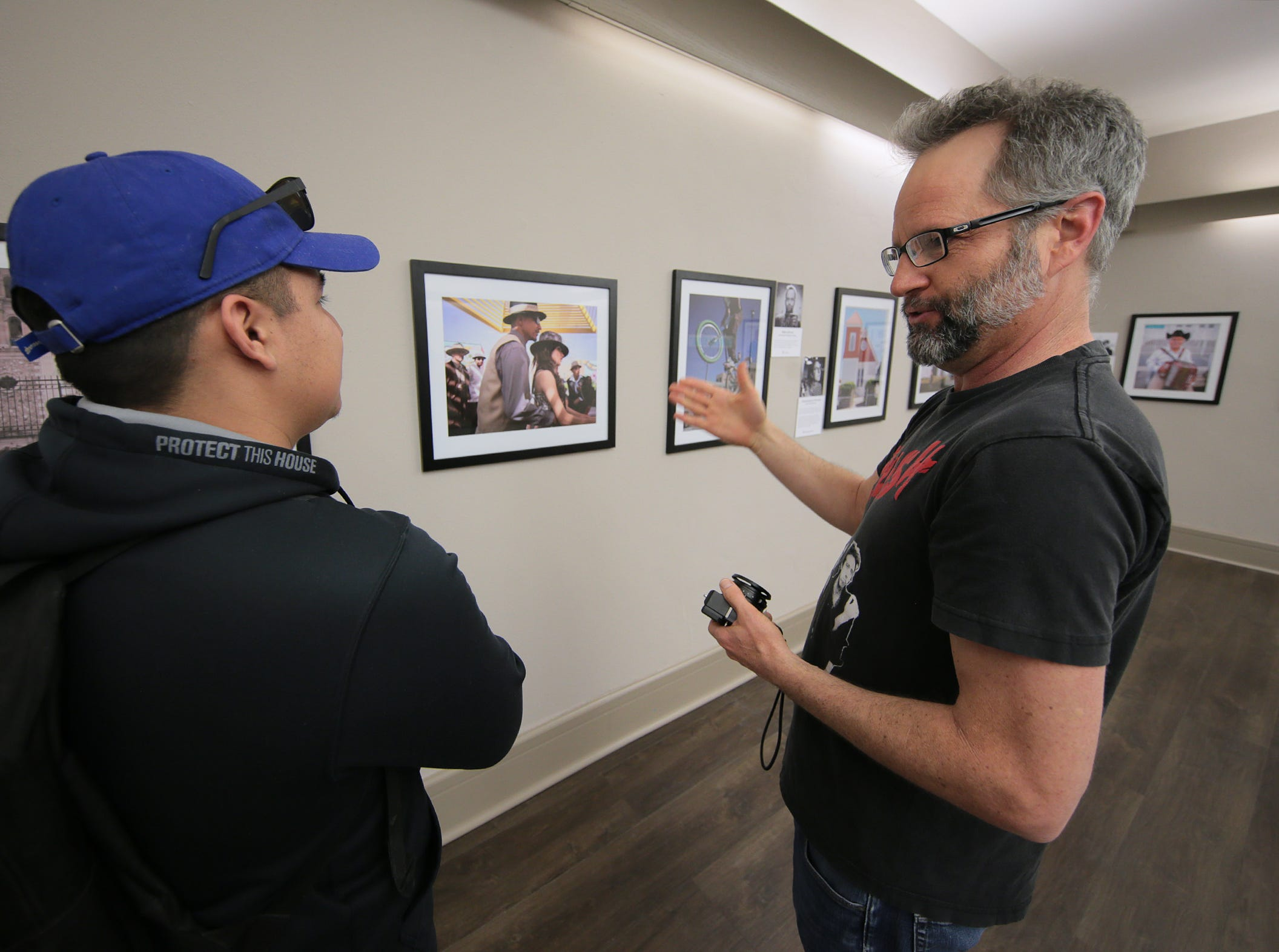 "Street photographer Patrick Craig, right, talks with Sergio Zamora at the opening of ""Rebirth Of Duranguito and Border Street, A Photo Exhibition"" at UTEP's Centennial Museum. The work of four street photographers will be on display at the gallery for two months."