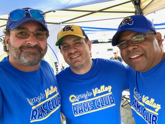 Rams fan Andre Jeanbart (center) poses with Conejo Valley Rams Club members Rob Jaffe (left) and Calvin Ward  at a pregame tailgate at the Coliseum.