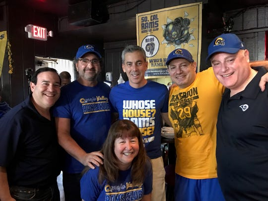 Rams fan Andre Jeanbart (second from right) poses with Rams chief Kevin Demoff (center) and other members of the Conejo Valley Rams Club.