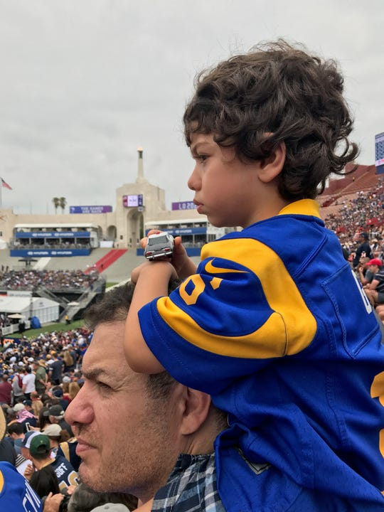 Andre Jeanbart of Westlake Vilage and his son Anthony watch the Rams together at the Coliseum.