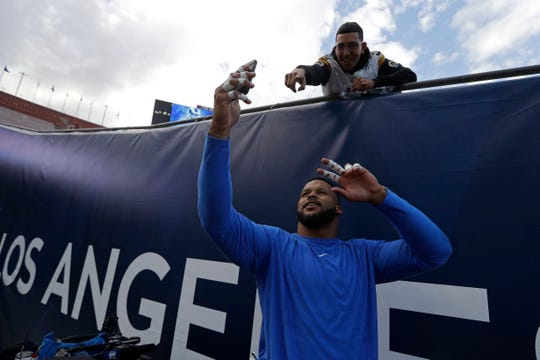 Rams defensive lineman Aaron Donald takes a picture with a fan before a home playoff game against the Cowboys.