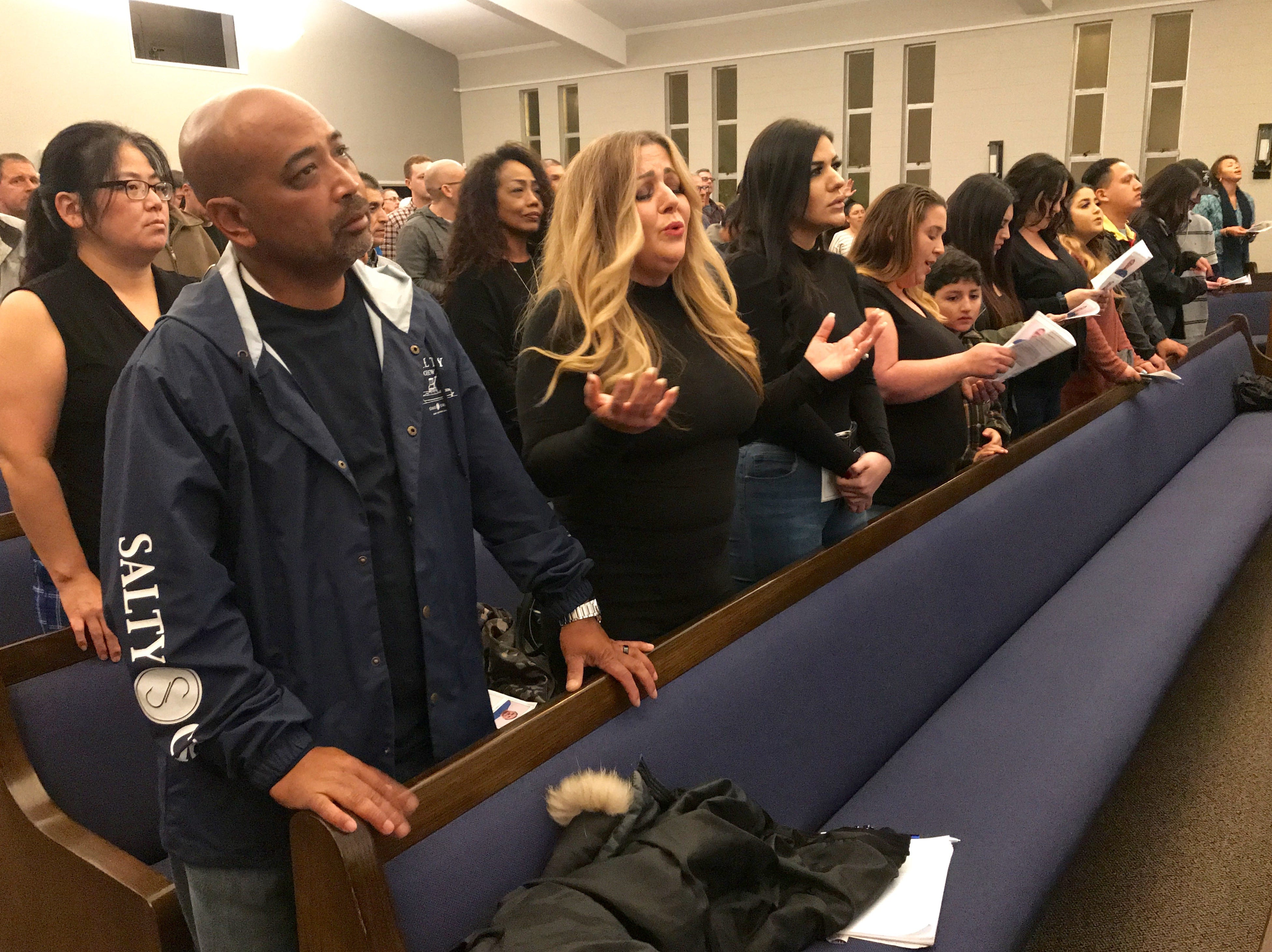 Family members of Ventura County Rescue Mission graduate JR Gutierrez sing during a ceremony to mark the occasion Jan. 29, 2019, in Oxnard.