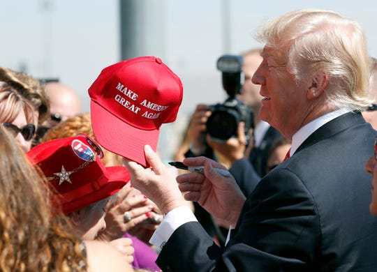"In this Aug. 23, 2017, file photo, President Donald Trump hands a signed ""Make America Great Again,"" hat back to a supporter in Reno."