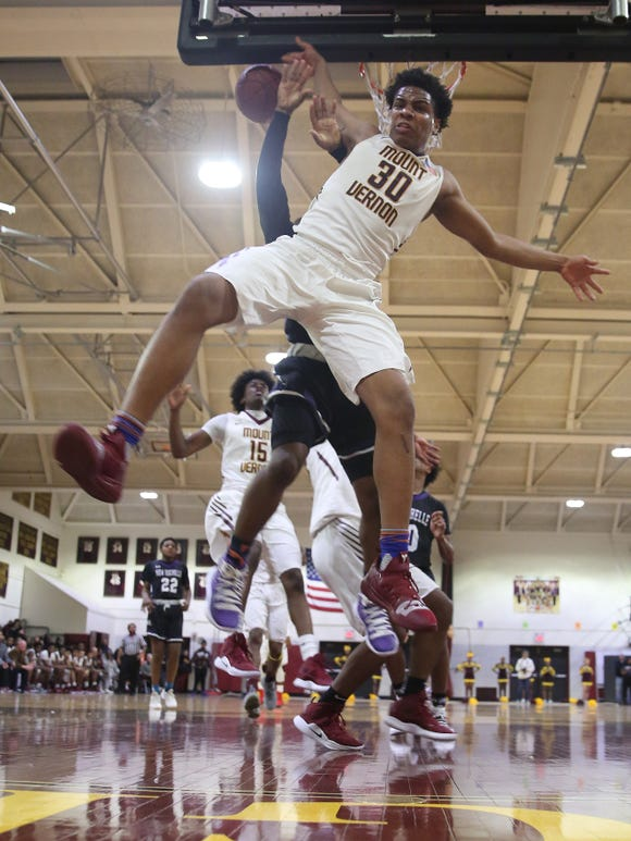 Mount Vernon's Troy Hupstead (30) comes down after blocking a shot by New Rochelle's Omari Walker (4) during boys basketball action at New Rochelle High School Jan. 31, 2019. Mount Vernon won the game 72-62.