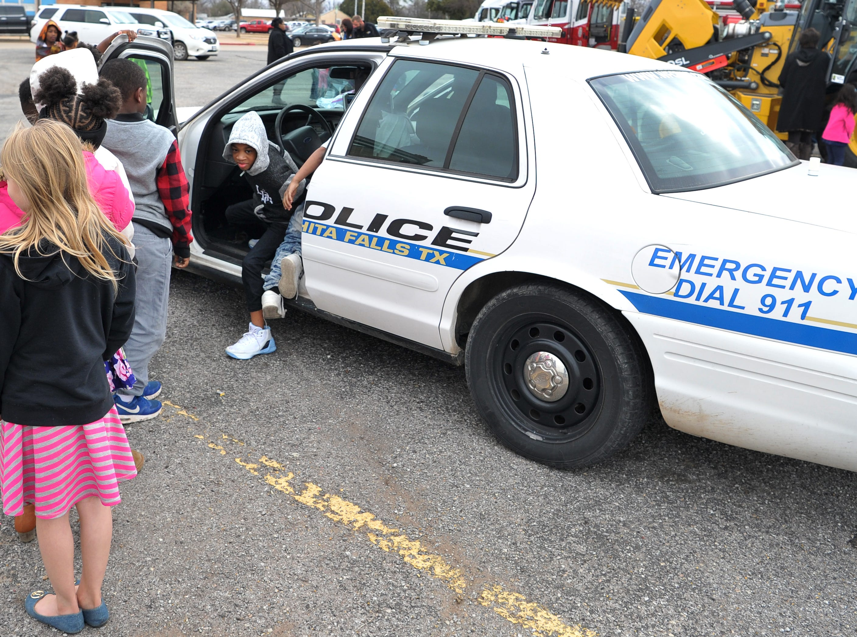 A line of students formed as kids waited their turn to sit in the driver's seat of a Wichita Falls police patrol car during career day Friday morning.